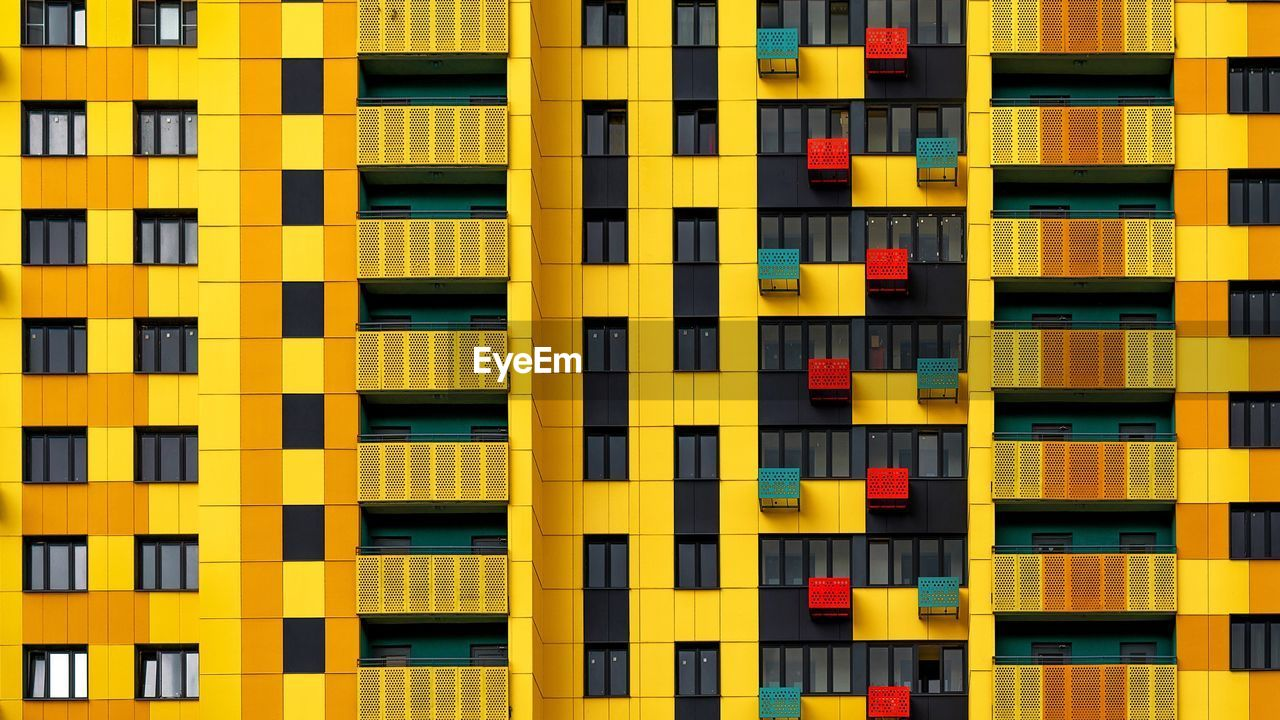 full frame, yellow, backgrounds, architecture, built structure, building exterior, no people, repetition, pattern, city, multi colored, building, modern, window, side by side, outdoors, in a row, residential district, day, design, apartment