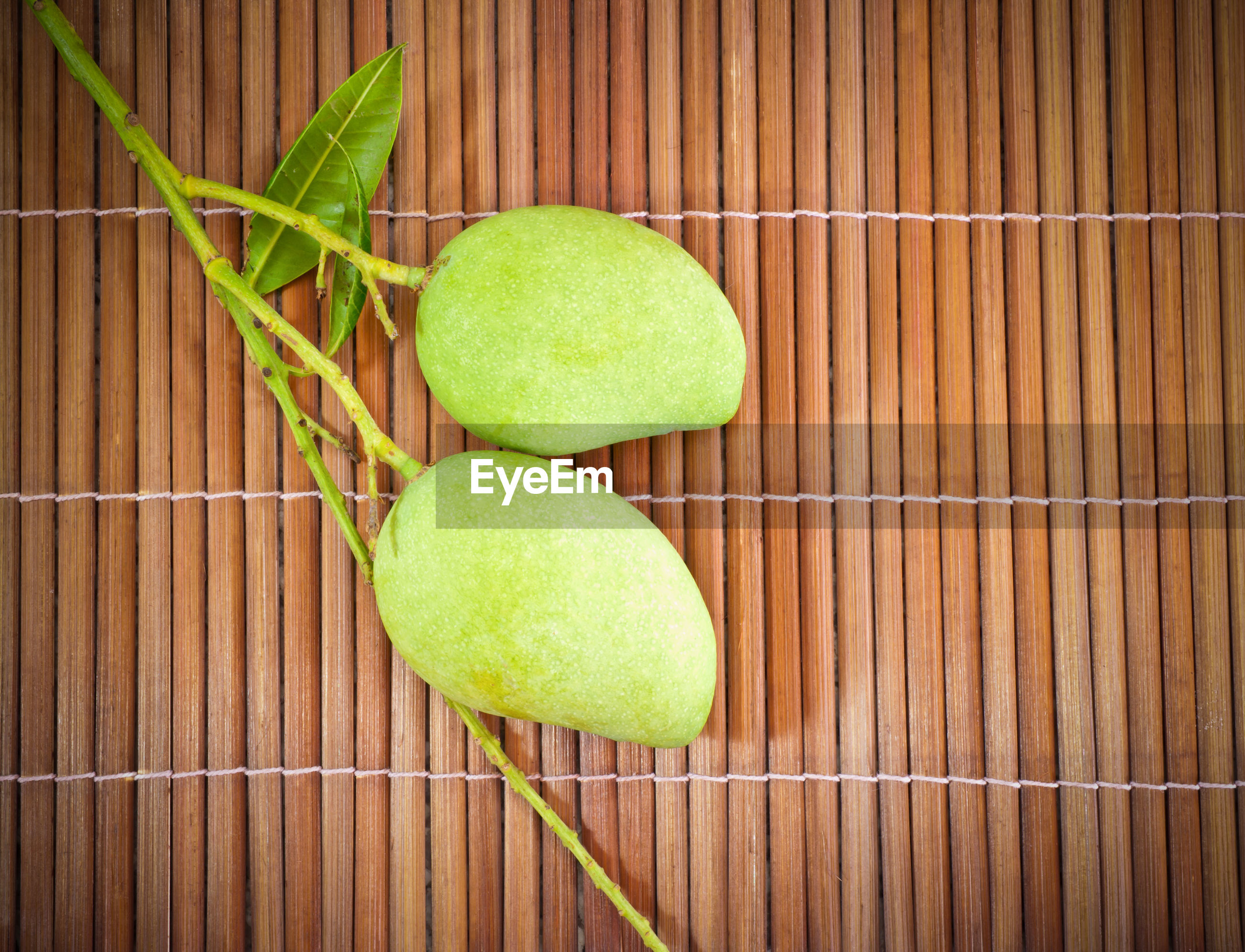 High angle view of raw mangoes on placemat