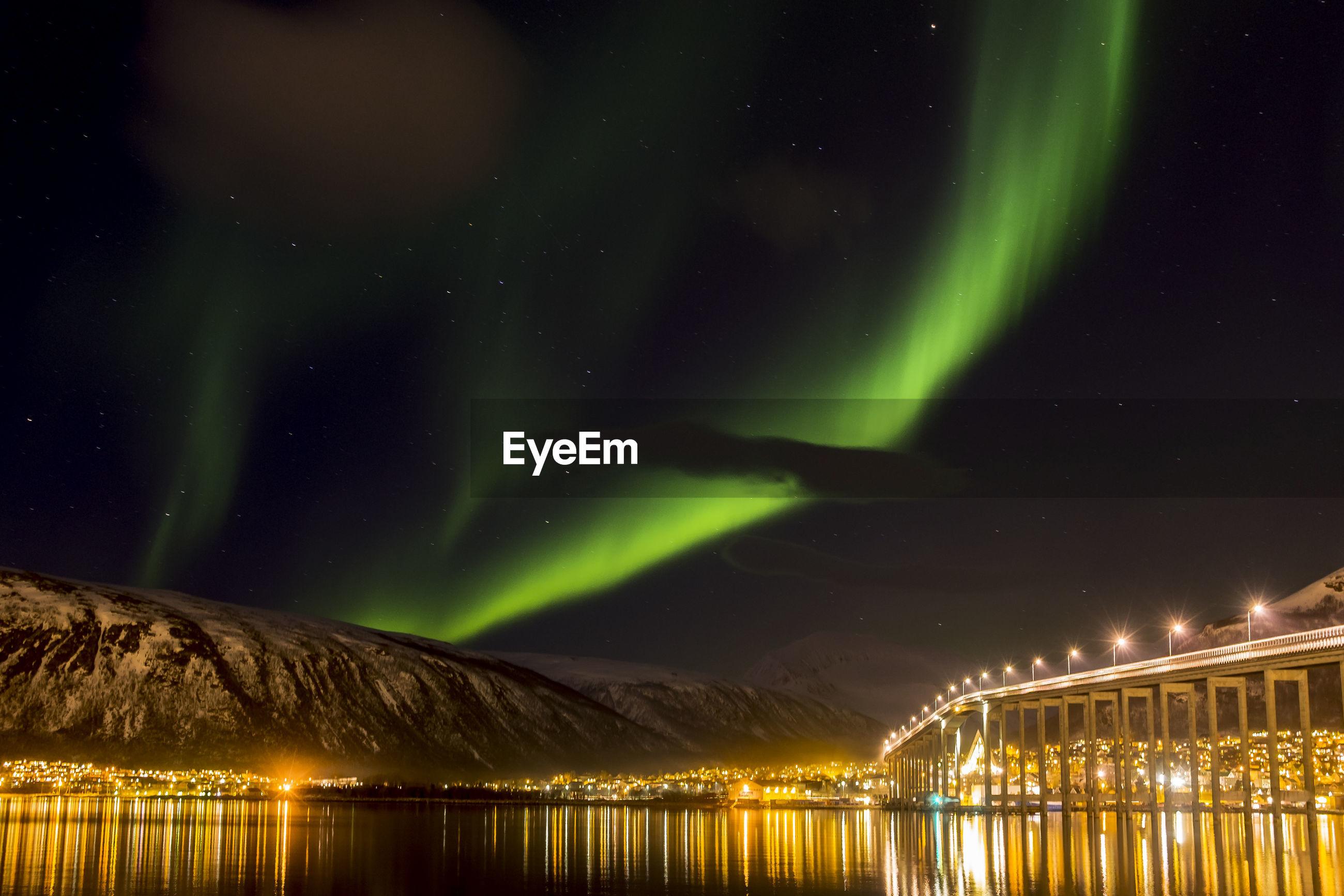Illuminated bridge over river against aurora borealis