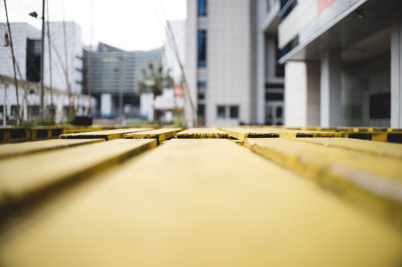 architecture, built structure, building exterior, selective focus, building, city, transportation, no people, day, outdoors, surface level, yellow, industry, nature, metal, street, sky, mode of transportation, construction industry, office