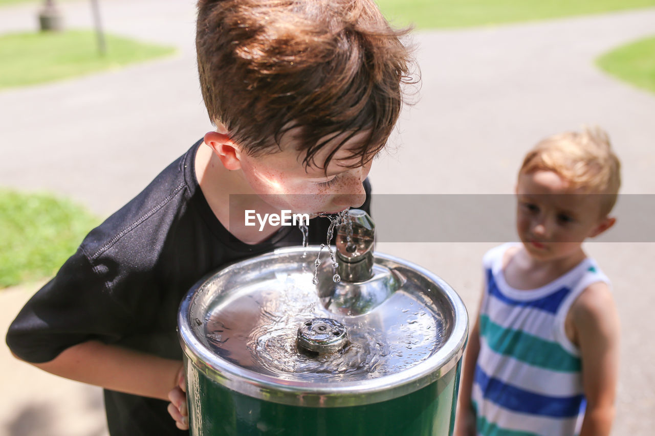 Cute boy looking at brother drinking water from container outdoors