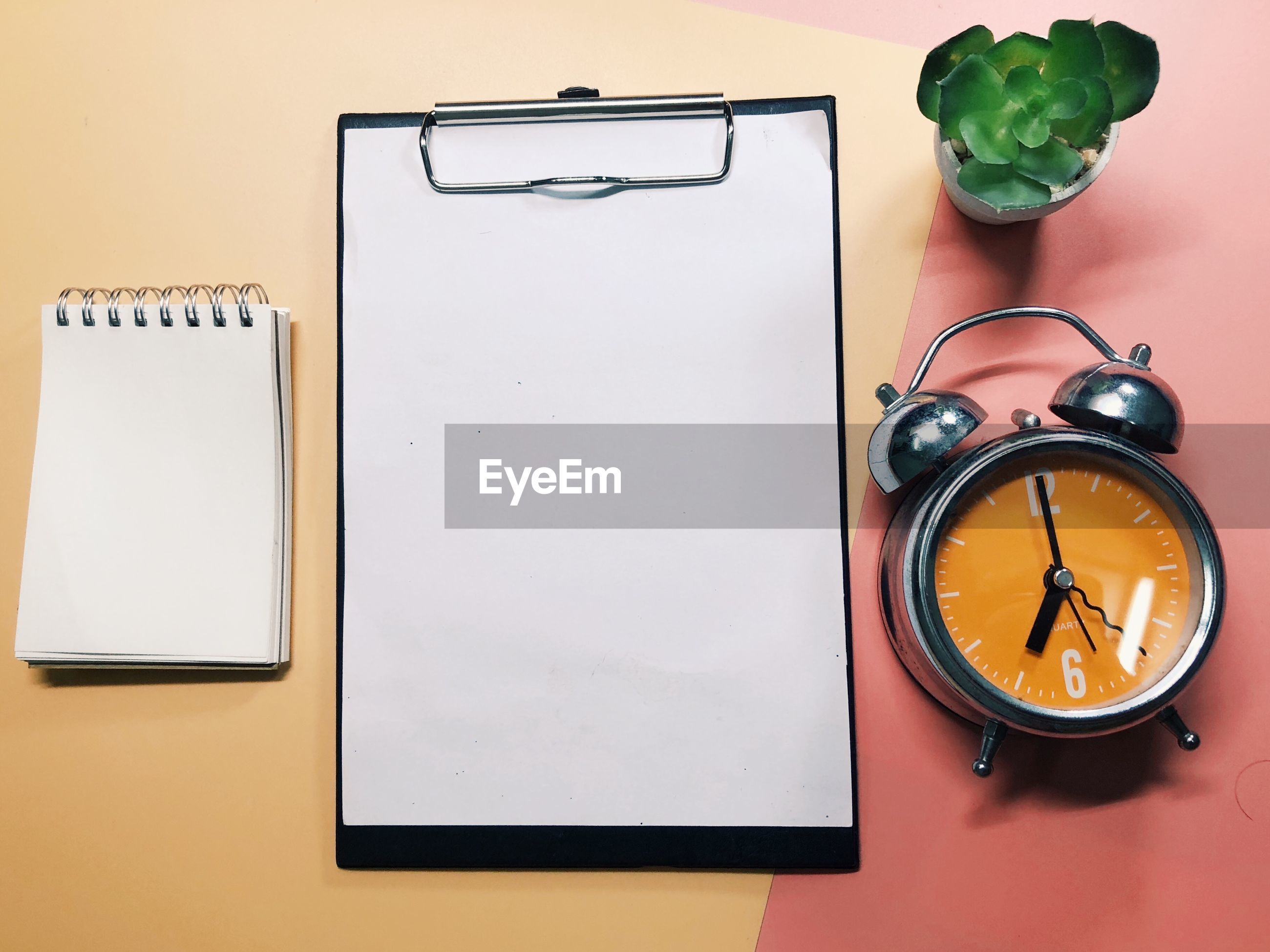Directly above shot of clipboard with alarm clock and note pad on colored background