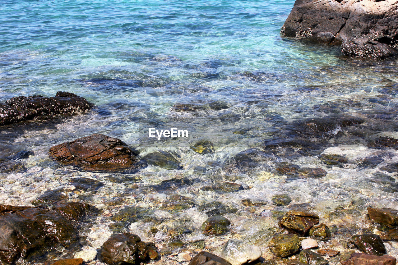 water, rock, rock - object, sea, solid, beauty in nature, nature, no people, day, land, tranquility, scenics - nature, high angle view, motion, beach, outdoors, idyllic, rock formation, tranquil scene, shallow, rocky coastline, turquoise colored, purity