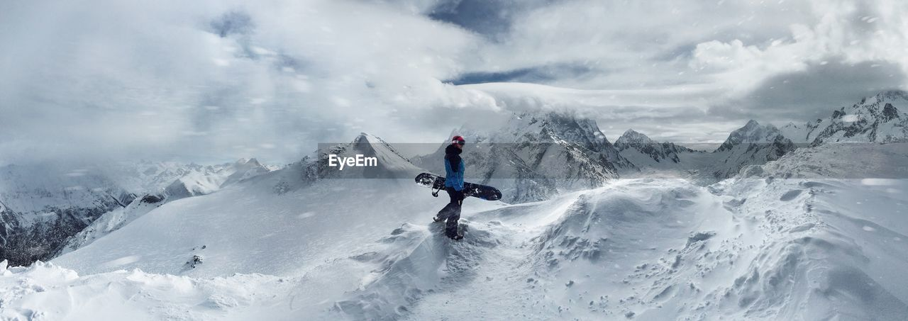 Side View Of Man Walking On Snowcapped Mountains Against Sky