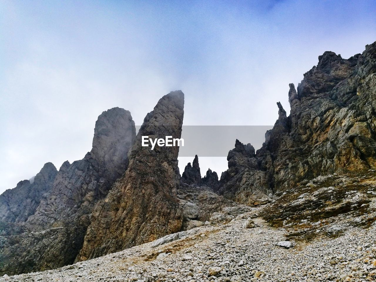 sky, rock, mountain, rock formation, rock - object, nature, solid, beauty in nature, low angle view, scenics - nature, tranquility, day, tranquil scene, mountain range, formation, outdoors, geology, no people, rocky mountains, land, mountain peak, eroded