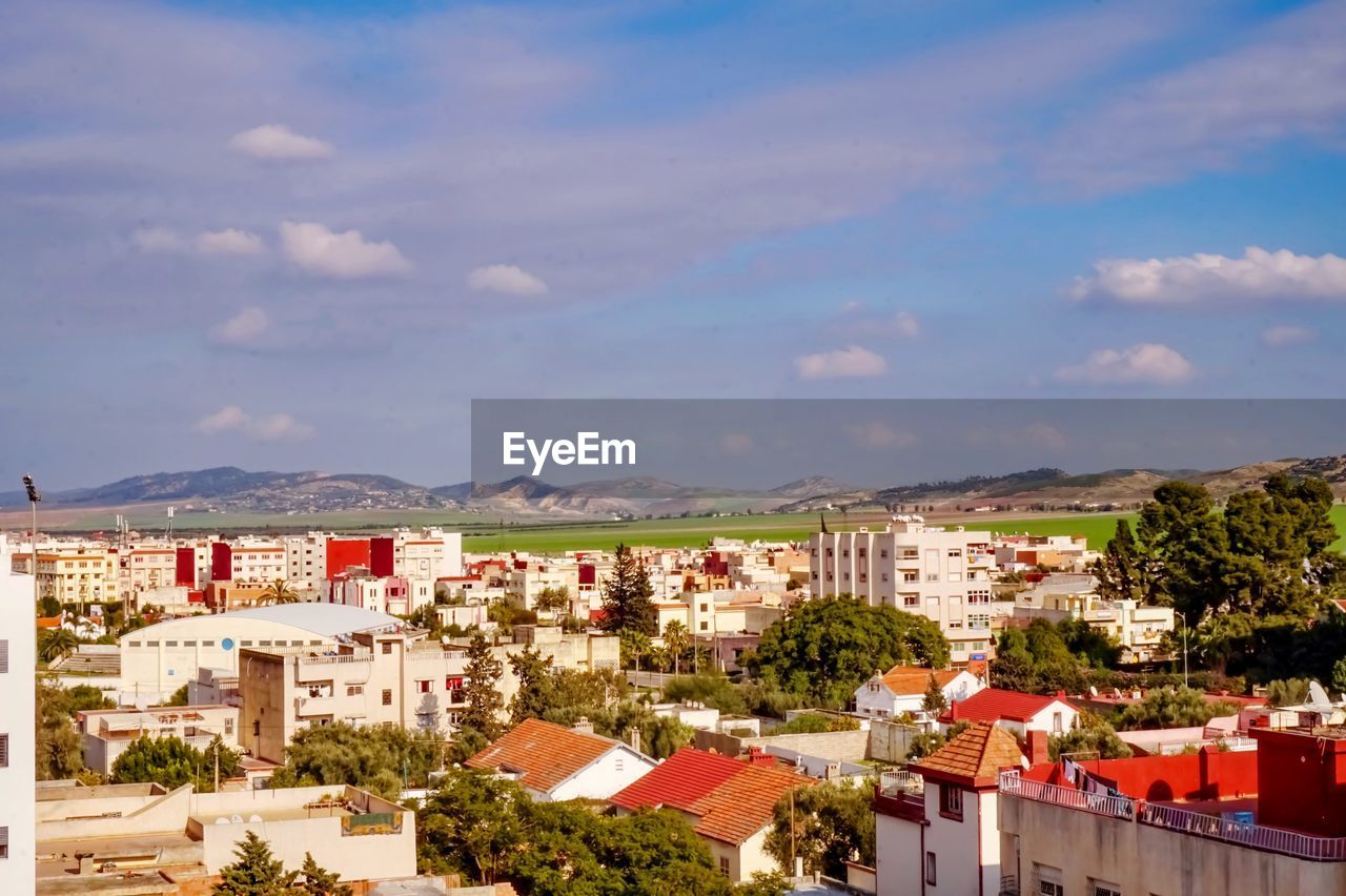 architecture, building exterior, built structure, building, residential district, city, cloud - sky, sky, nature, day, cityscape, no people, high angle view, tree, house, outdoors, town, plant, townscape, settlement, apartment