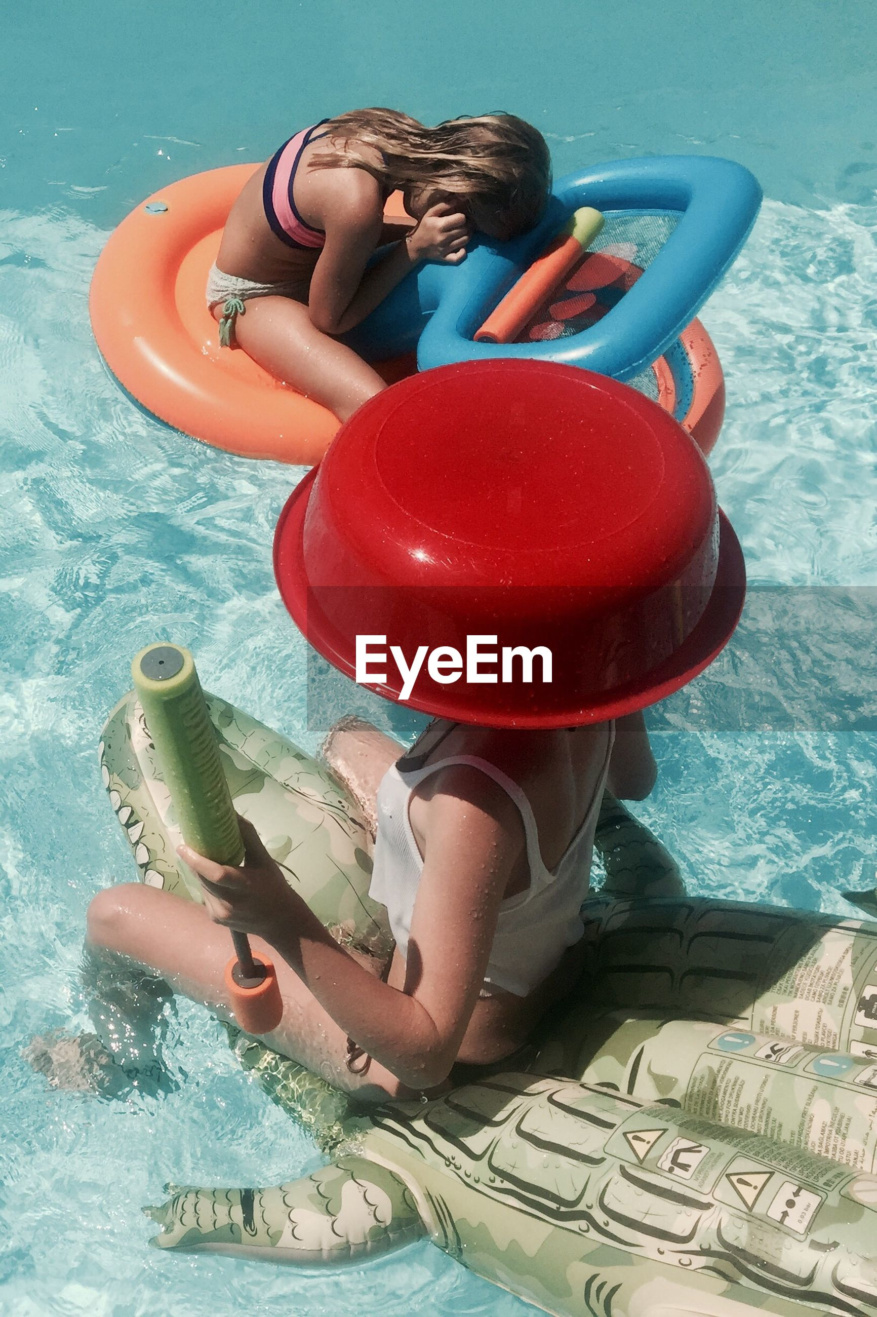 inflatable ring, childhood, inflatable, water, real people, leisure activity, swimming pool, full length, two people, day, fun, happiness, togetherness, floating on water, sitting, elementary age, outdoors, boys, playing, lifestyles, bonding, girls, red, smiling, water slide, young adult