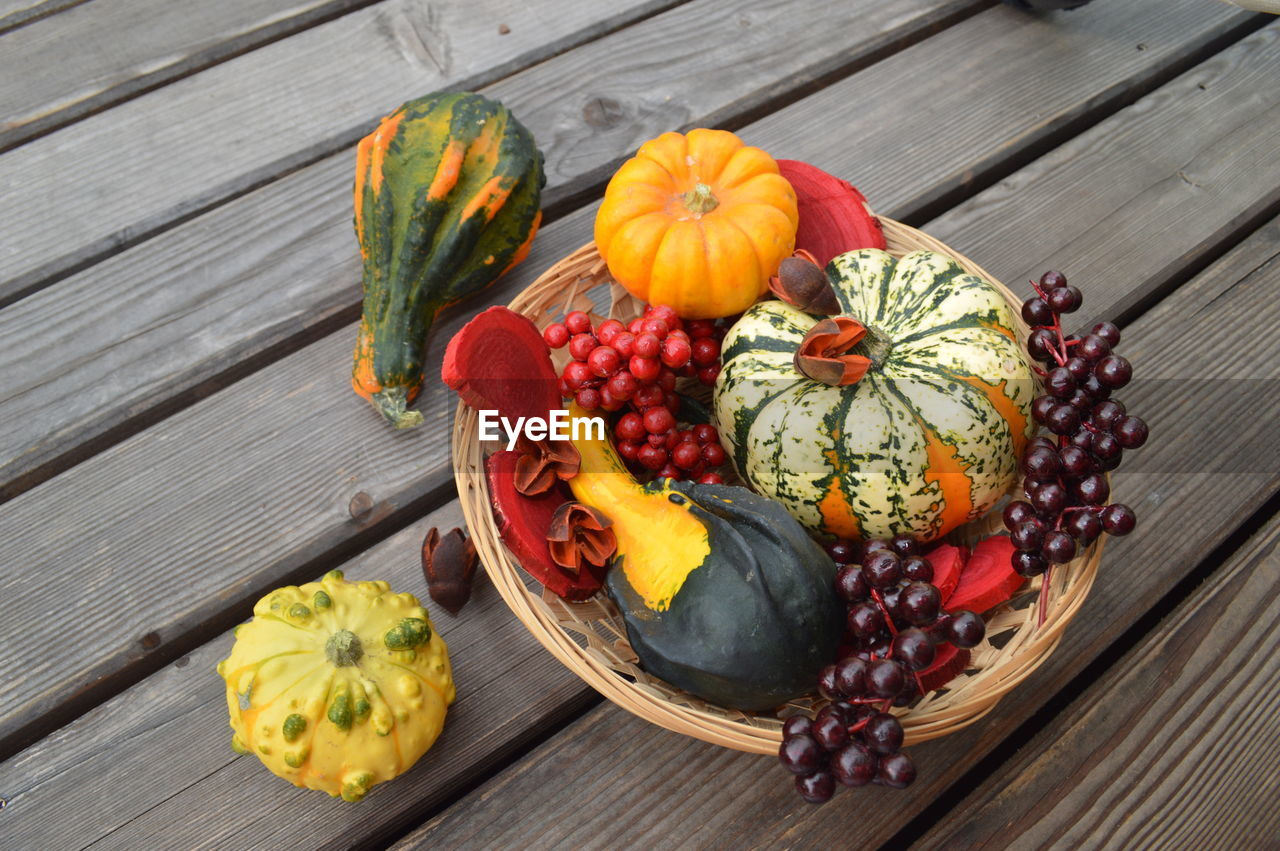food and drink, food, healthy eating, freshness, fruit, wellbeing, variation, wood - material, choice, high angle view, table, pumpkin, no people, vegetable, still life, directly above, nature, multi colored, flower, leaf