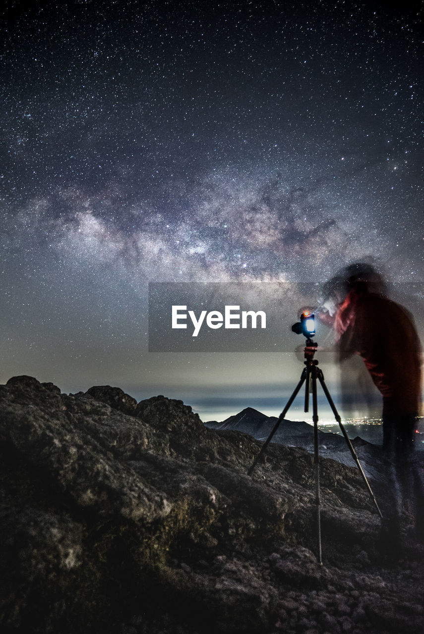 Double Exposure Of Man Photographing Sky At Night