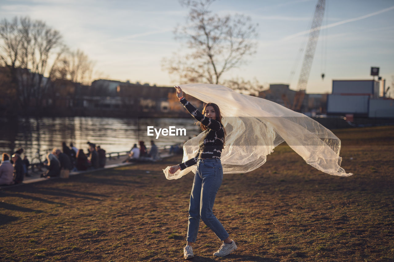 real people, sky, leisure activity, full length, nature, standing, women, lifestyles, casual clothing, people, adult, land, young adult, focus on foreground, water, young women, incidental people, men, dancing, outdoors, human arm, arms raised