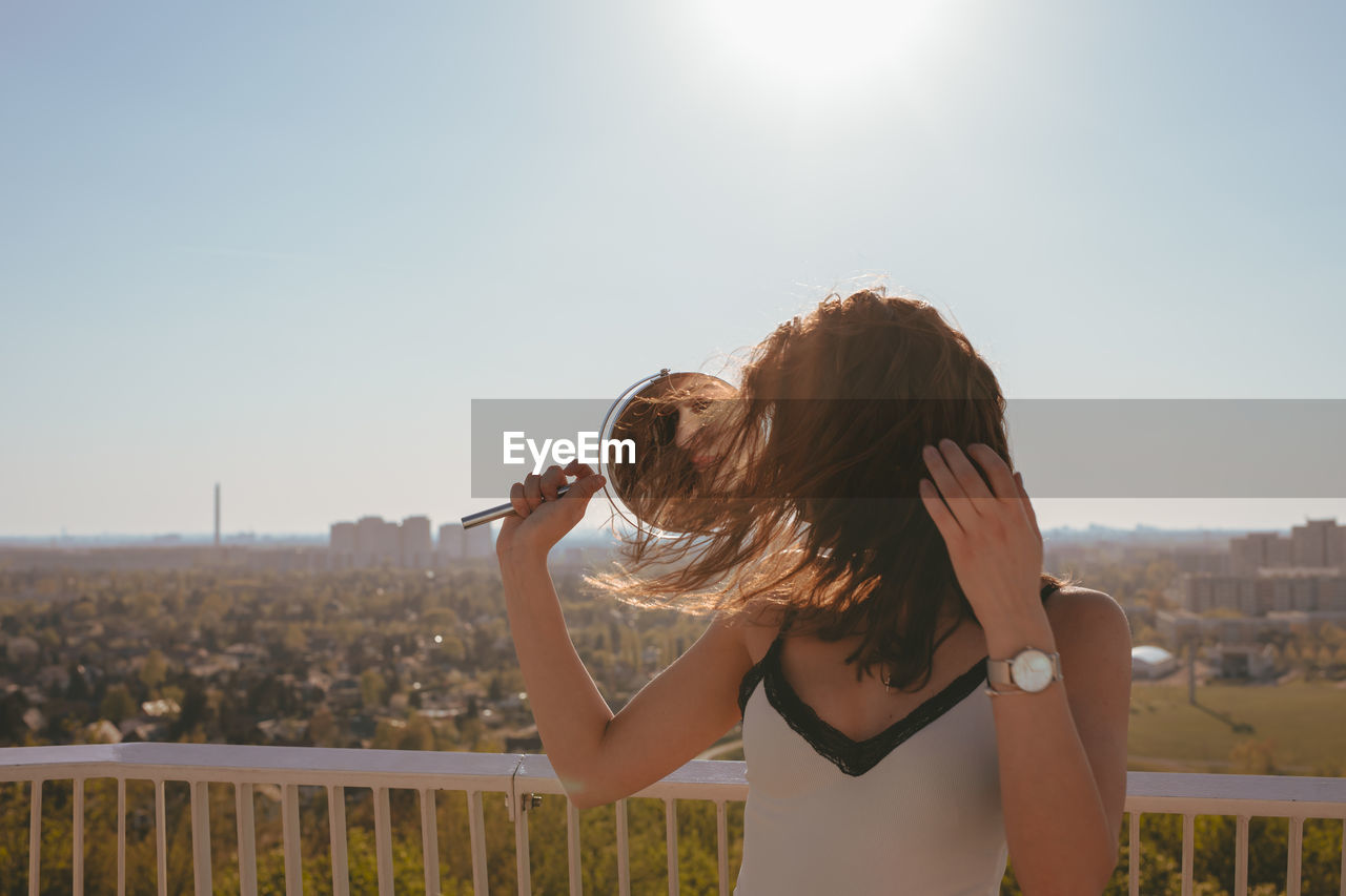 sky, sunlight, one person, hairstyle, long hair, hair, real people, nature, young adult, young women, leisure activity, lifestyles, architecture, building exterior, adult, day, standing, women, lens flare, fashion, outdoors, beautiful woman, bright, cityscape