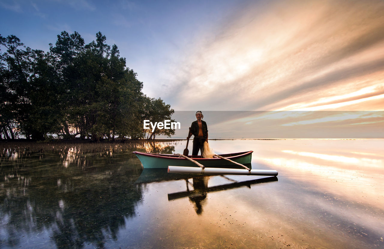 Man standing in boat on sea during sunset