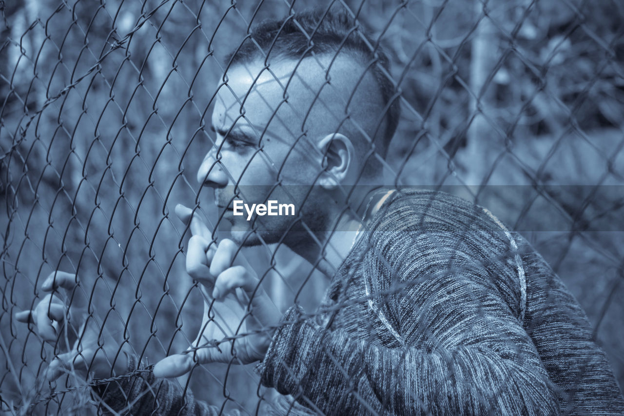 Young man looking through chainlink fence