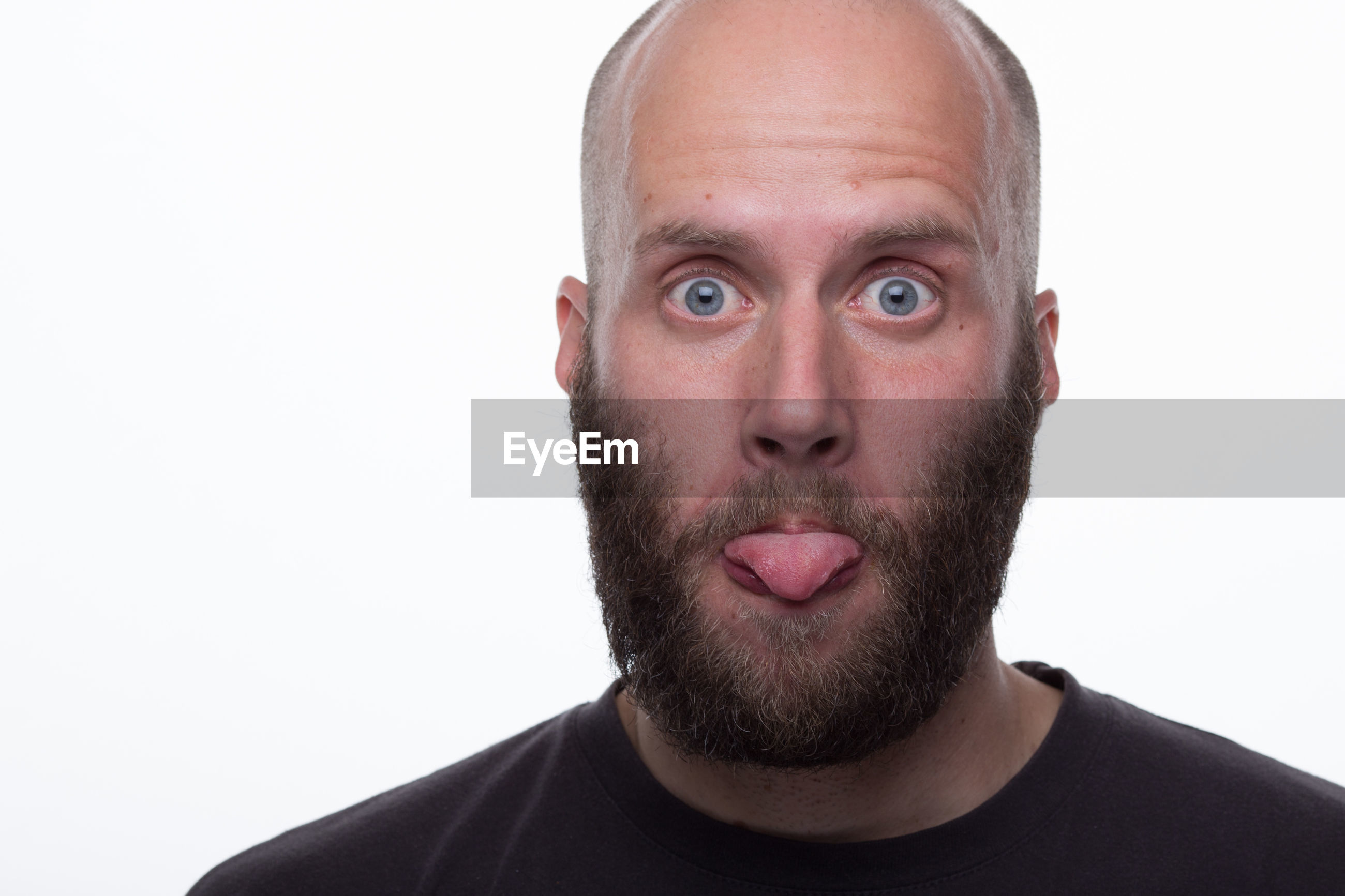 Close-up portrait of bearded man sticking out tongue against white background
