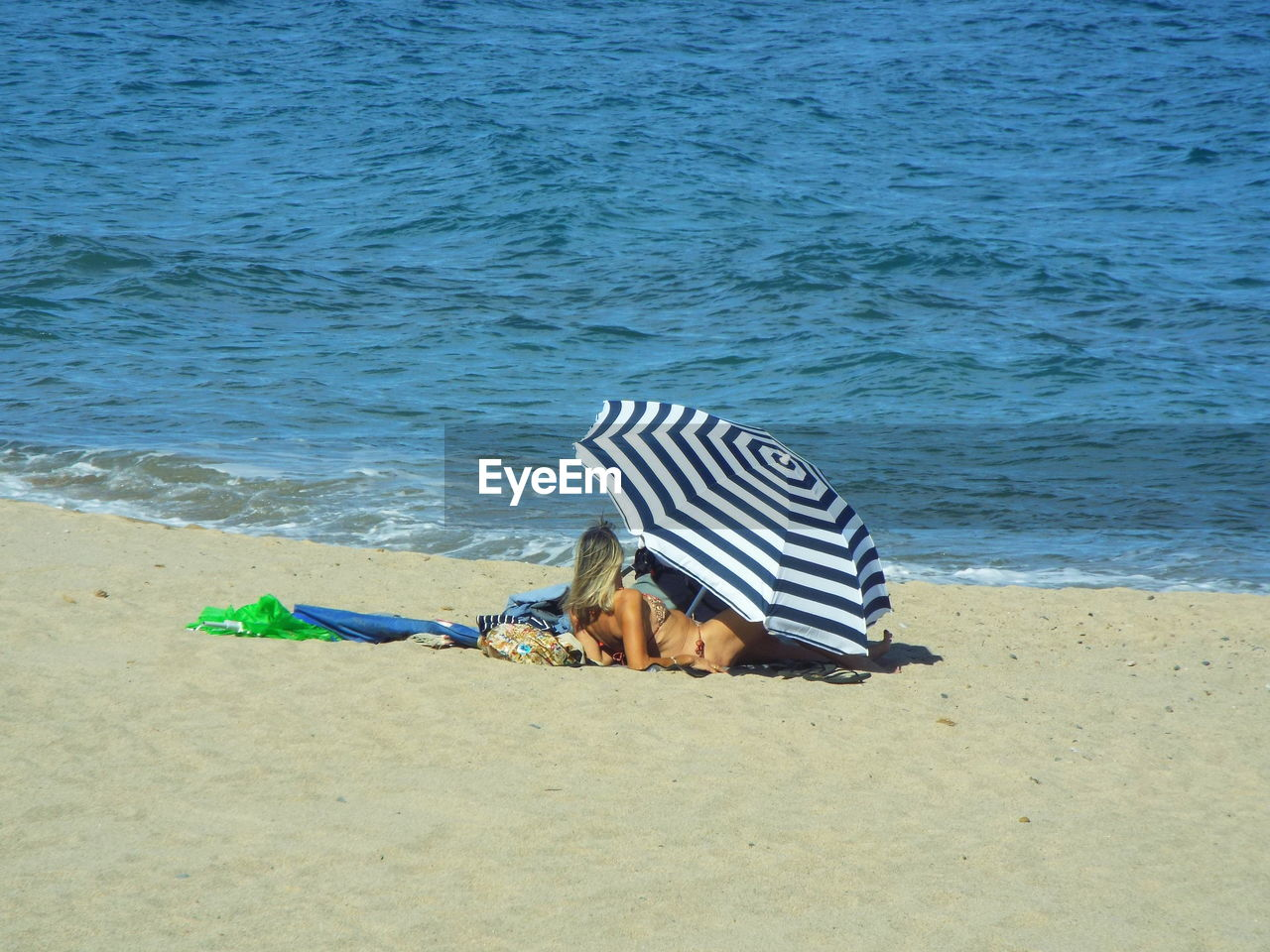 Woman Relaxing At Beach In Parasol By Sea