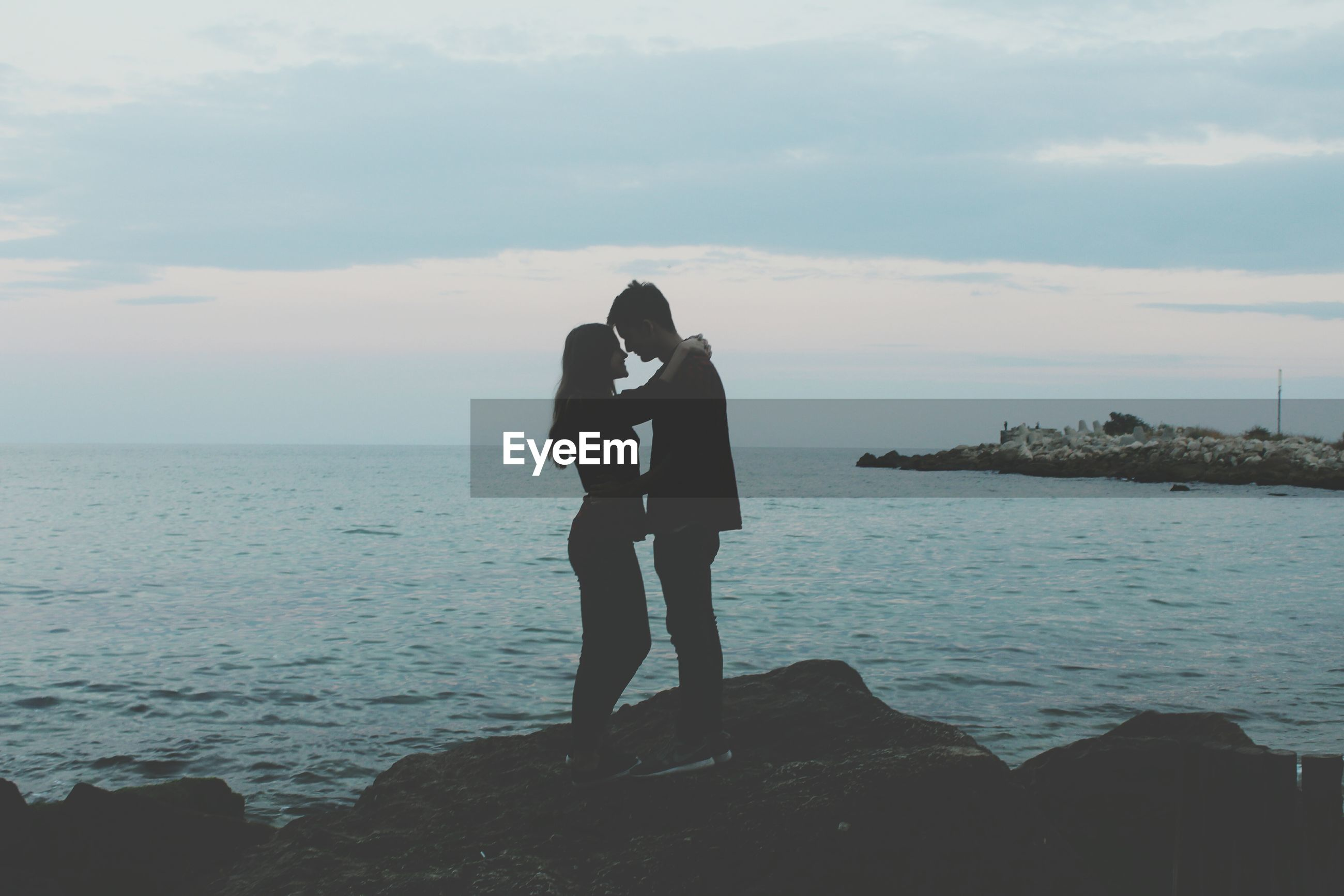 Couple kissing on sea against sky