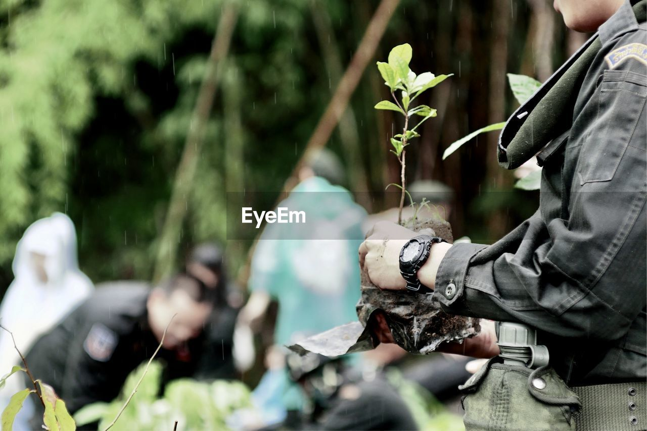 real people, plant, military, day, nature, focus on foreground, people, lifestyles, government, men, growth, holding, outdoors, armed forces, army soldier, protection, leaf, selective focus, leisure activity, weapon, uniform