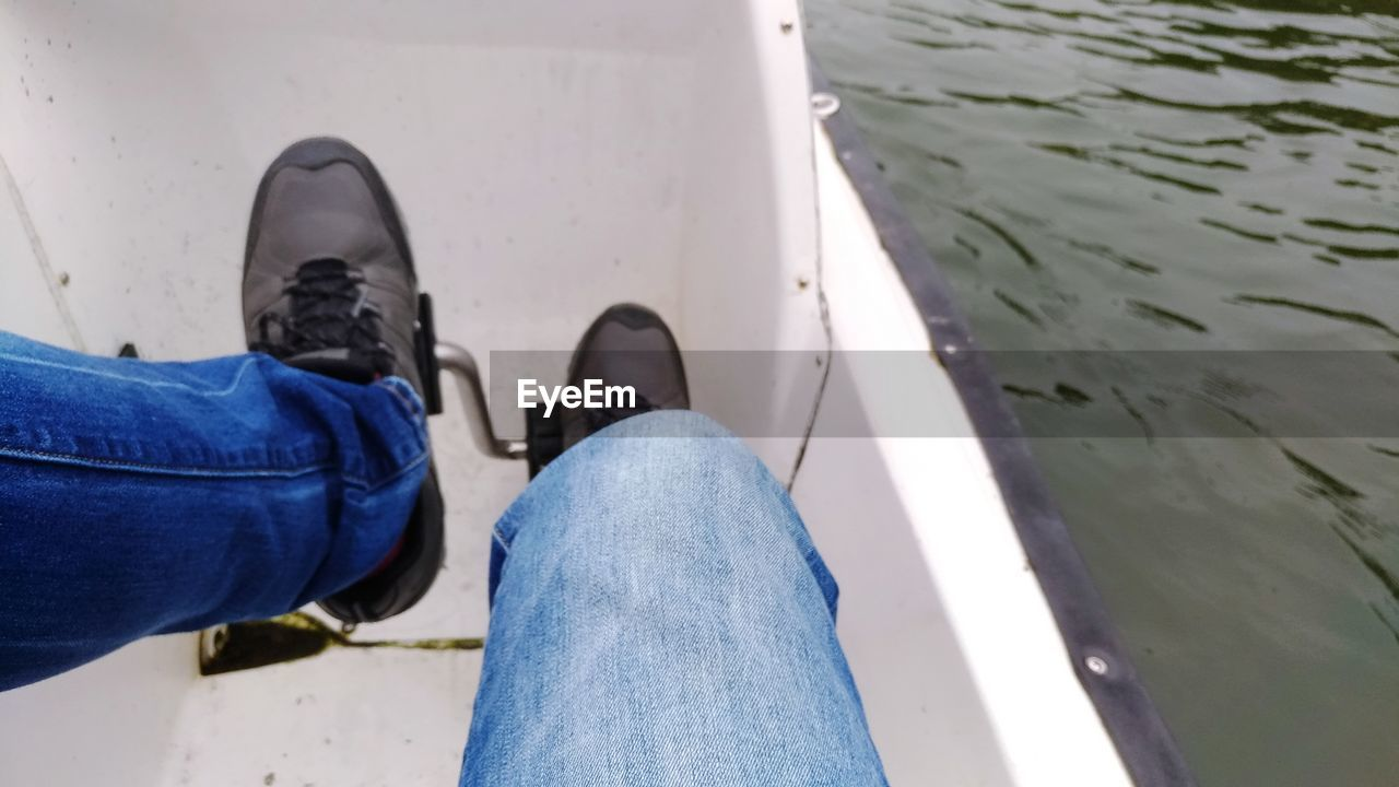 low section, human leg, jeans, body part, human body part, shoe, real people, lifestyles, one person, personal perspective, leisure activity, men, day, high angle view, casual clothing, water, outdoors, nature, unrecognizable person, human foot, human limb
