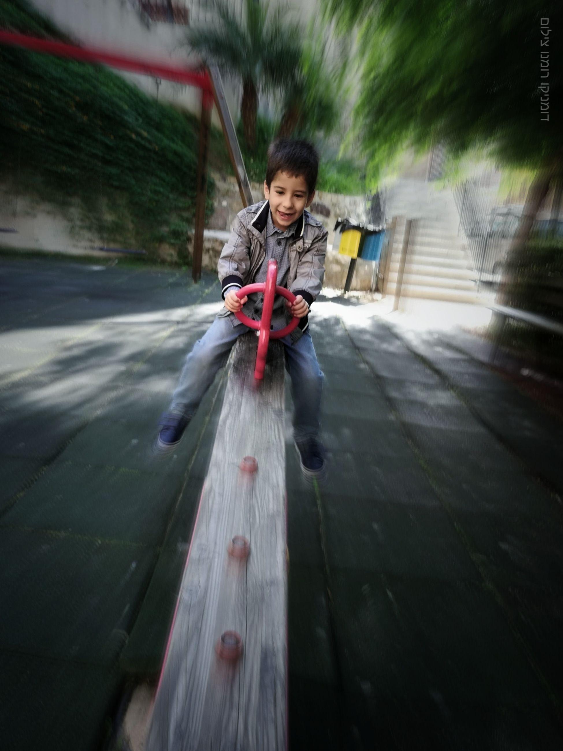 Full length of boy on seesaw