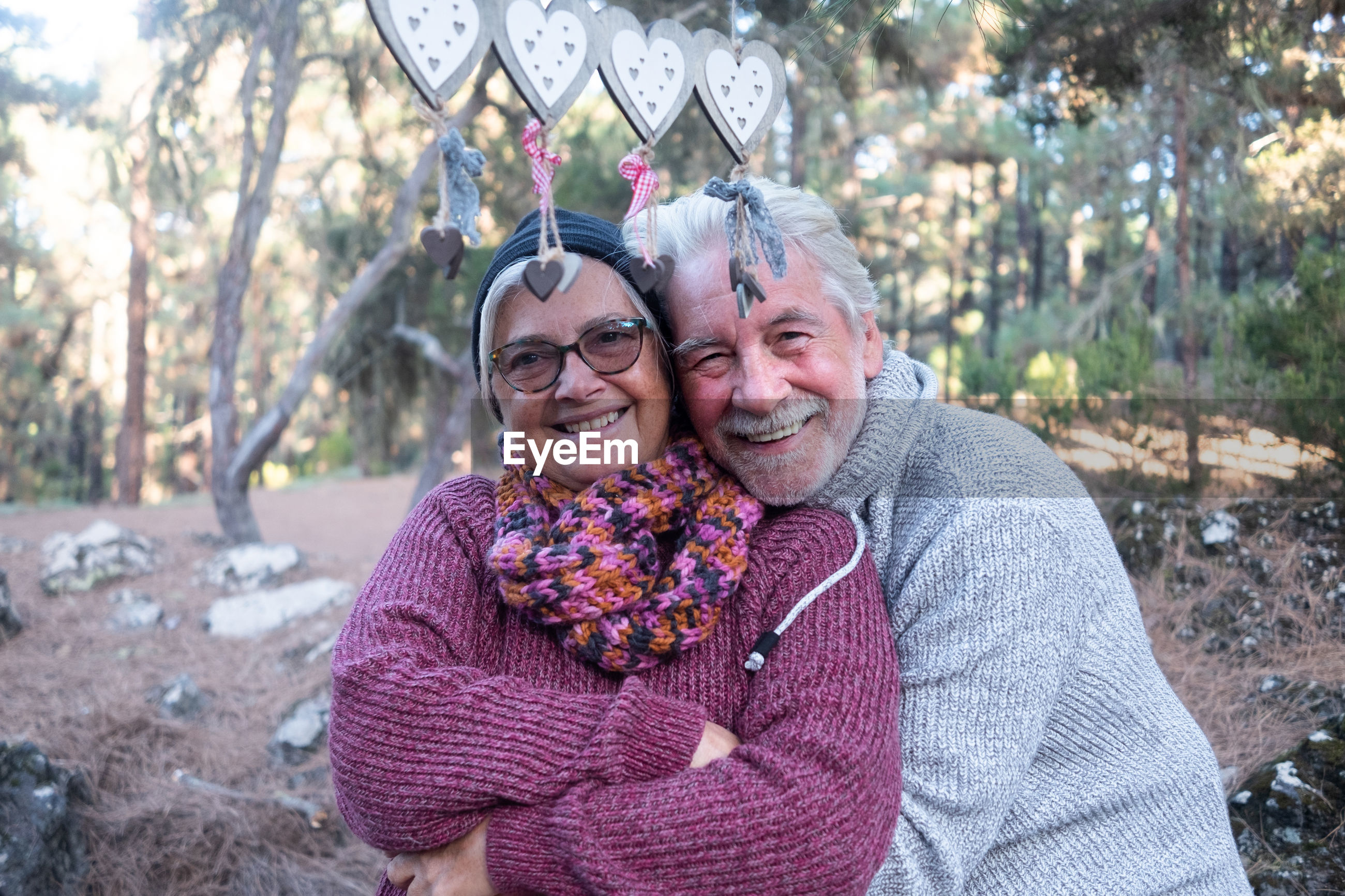 Portrait of smiling man and woman embracing against trees in forest