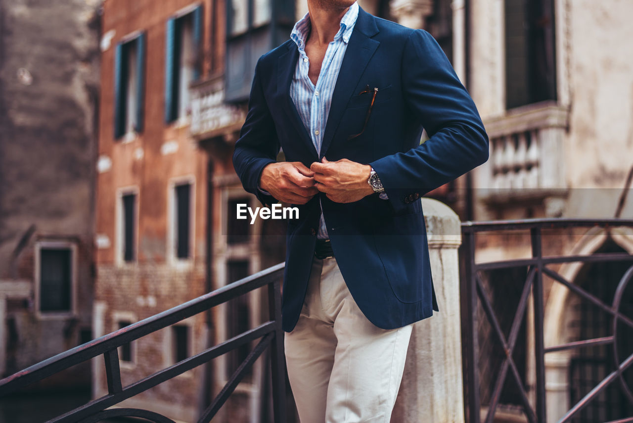 Midsection of man wearing blazer while standing against building