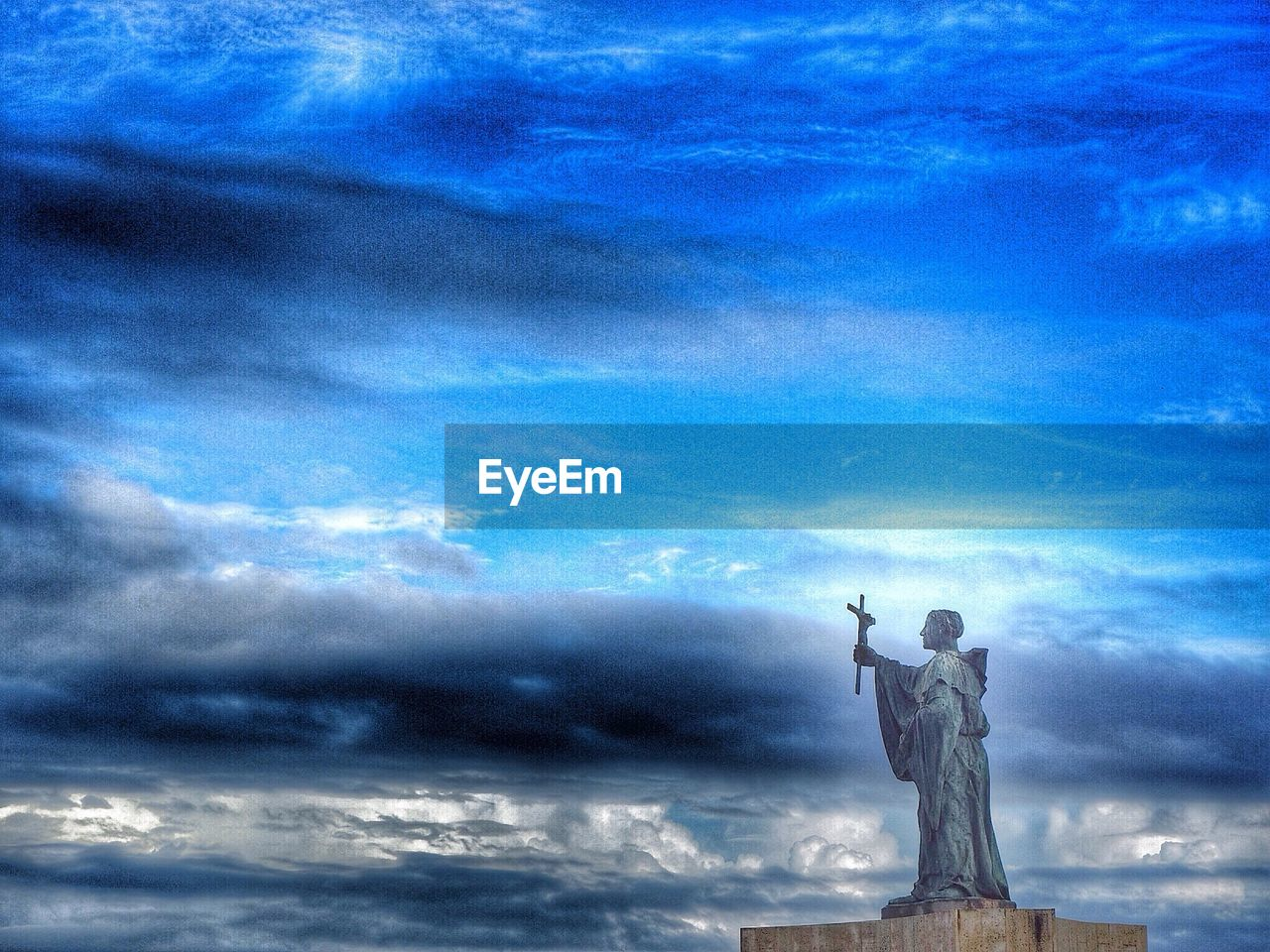 Statue With Crucifix Against Sky