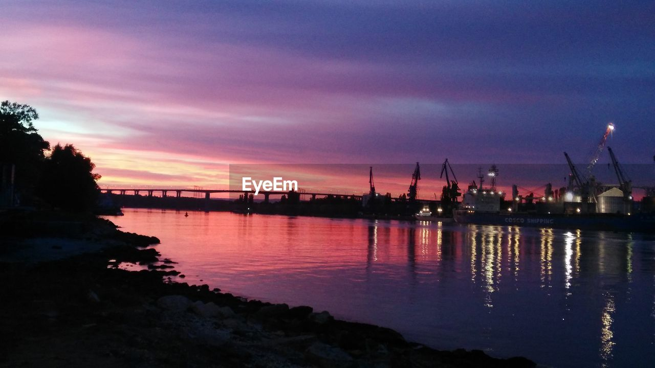 water, sky, sunset, cloud - sky, reflection, illuminated, no people, architecture, nature, transportation, waterfront, sea, dusk, night, outdoors, industry, orange color, scenics - nature, built structure, construction equipment