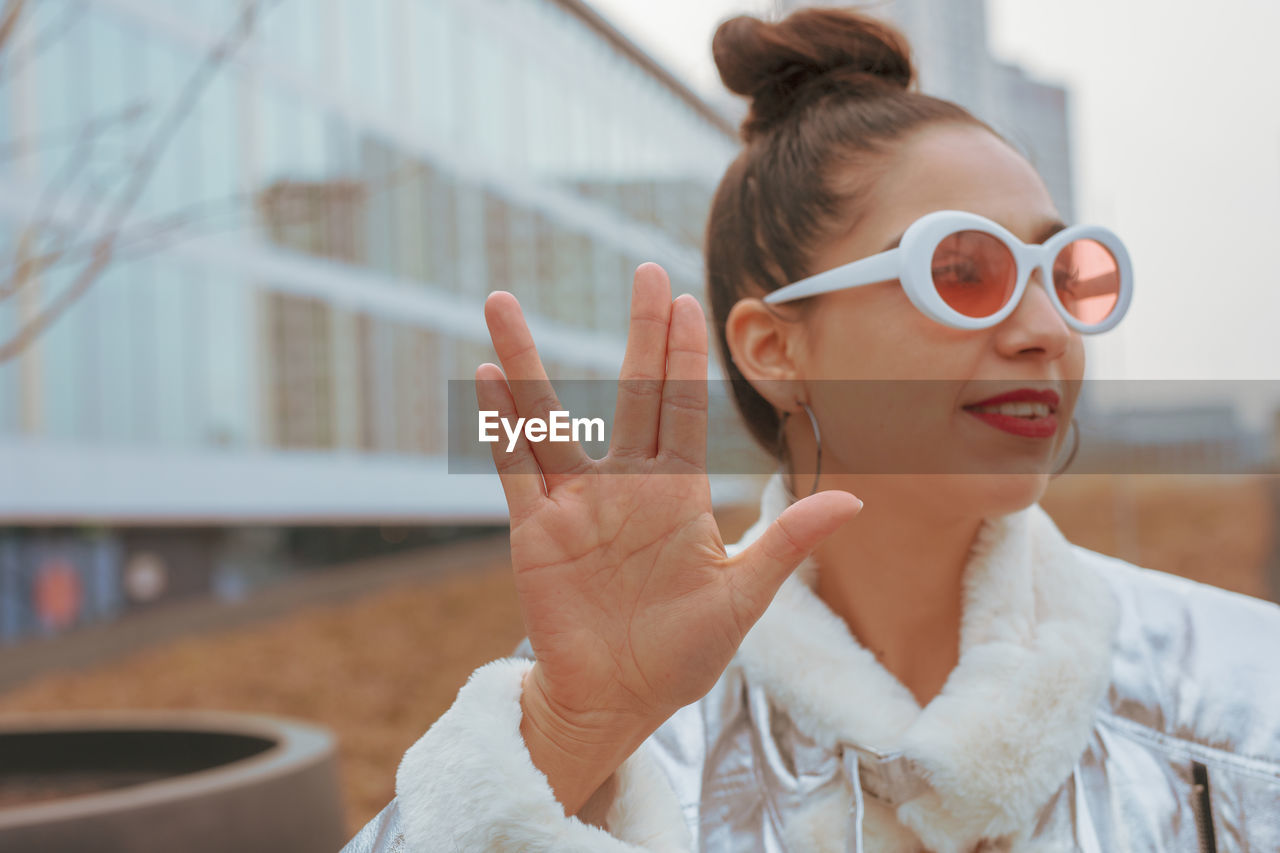 real people, focus on foreground, one person, glasses, headshot, sunglasses, lifestyles, portrait, leisure activity, young adult, front view, gesturing, fashion, women, adult, architecture, day, young women, outdoors, hairstyle, beautiful woman, finger