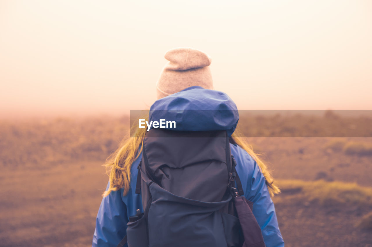 Rear view of woman with backpack standing on field during foggy weather