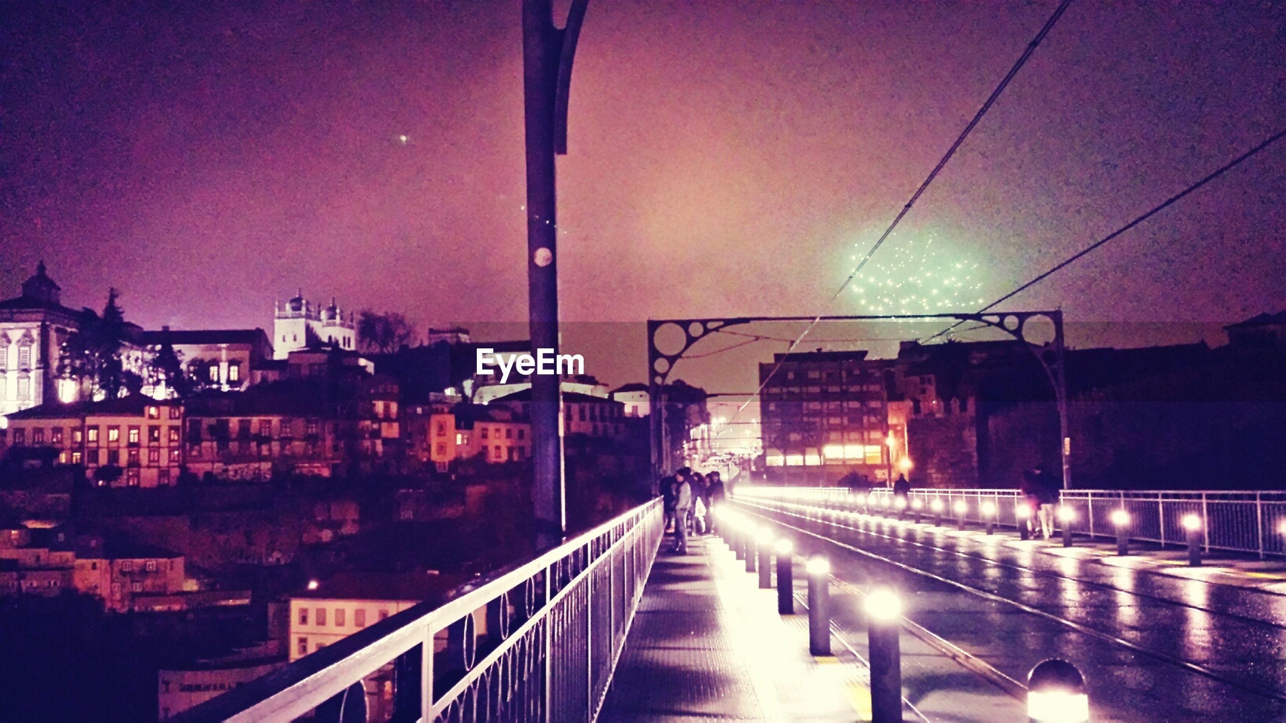 Illuminated street against sky at night in city
