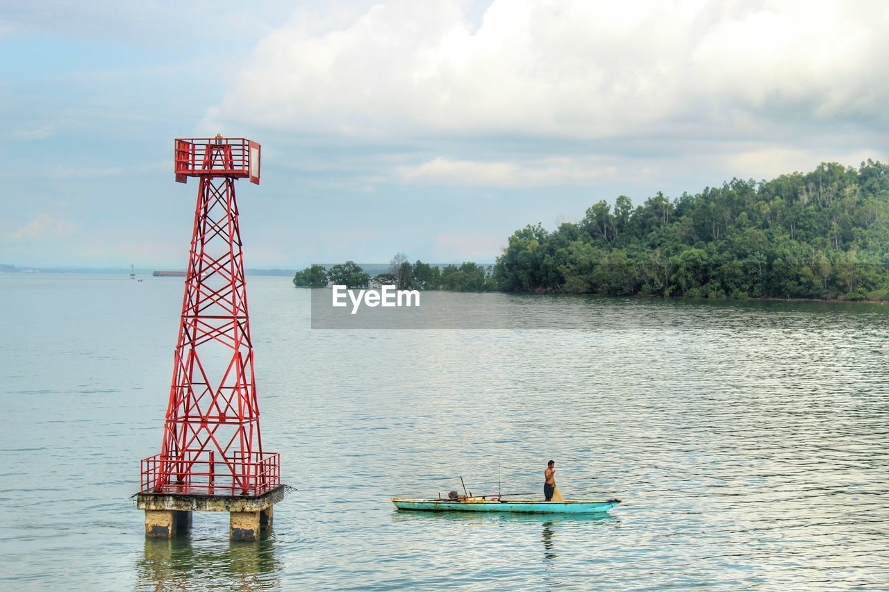 Shirtless man sailing boat in river against cloudy sky