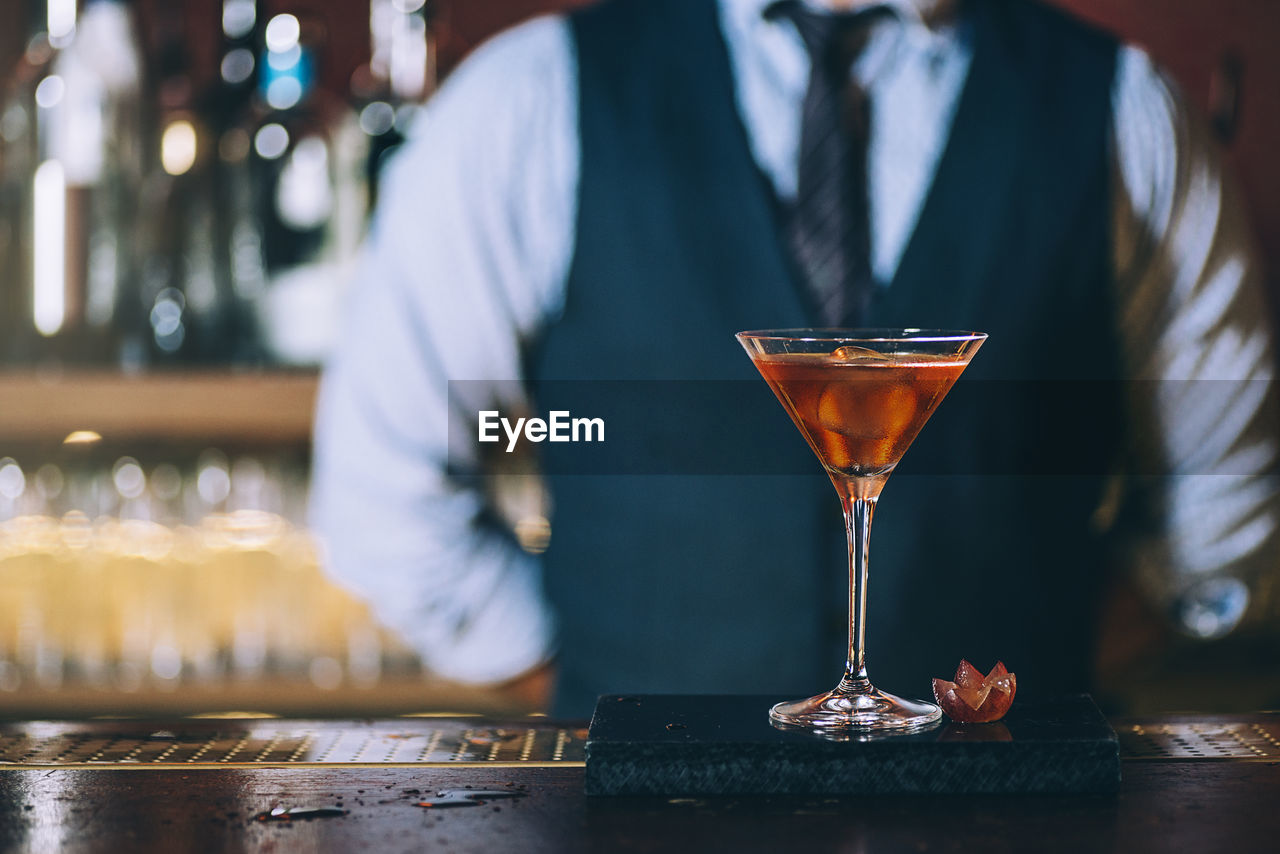Midsection of mature bartender standing by cocktail on bar counter
