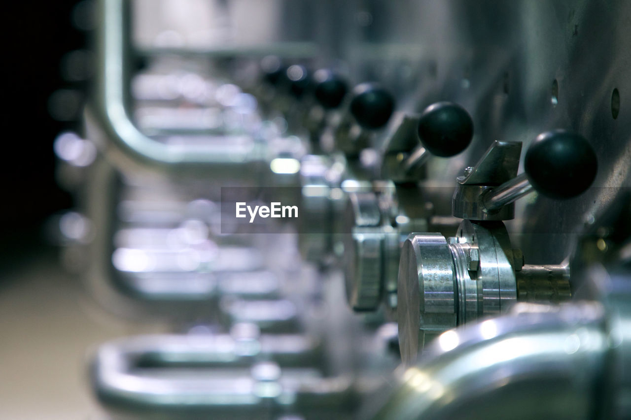 selective focus, machinery, metal, indoors, close-up, no people, in a row, machine part, equipment, technology, industry, food and drink, steel, repetition, business, silver colored, mode of transportation, pattern, manufacturing equipment, green color