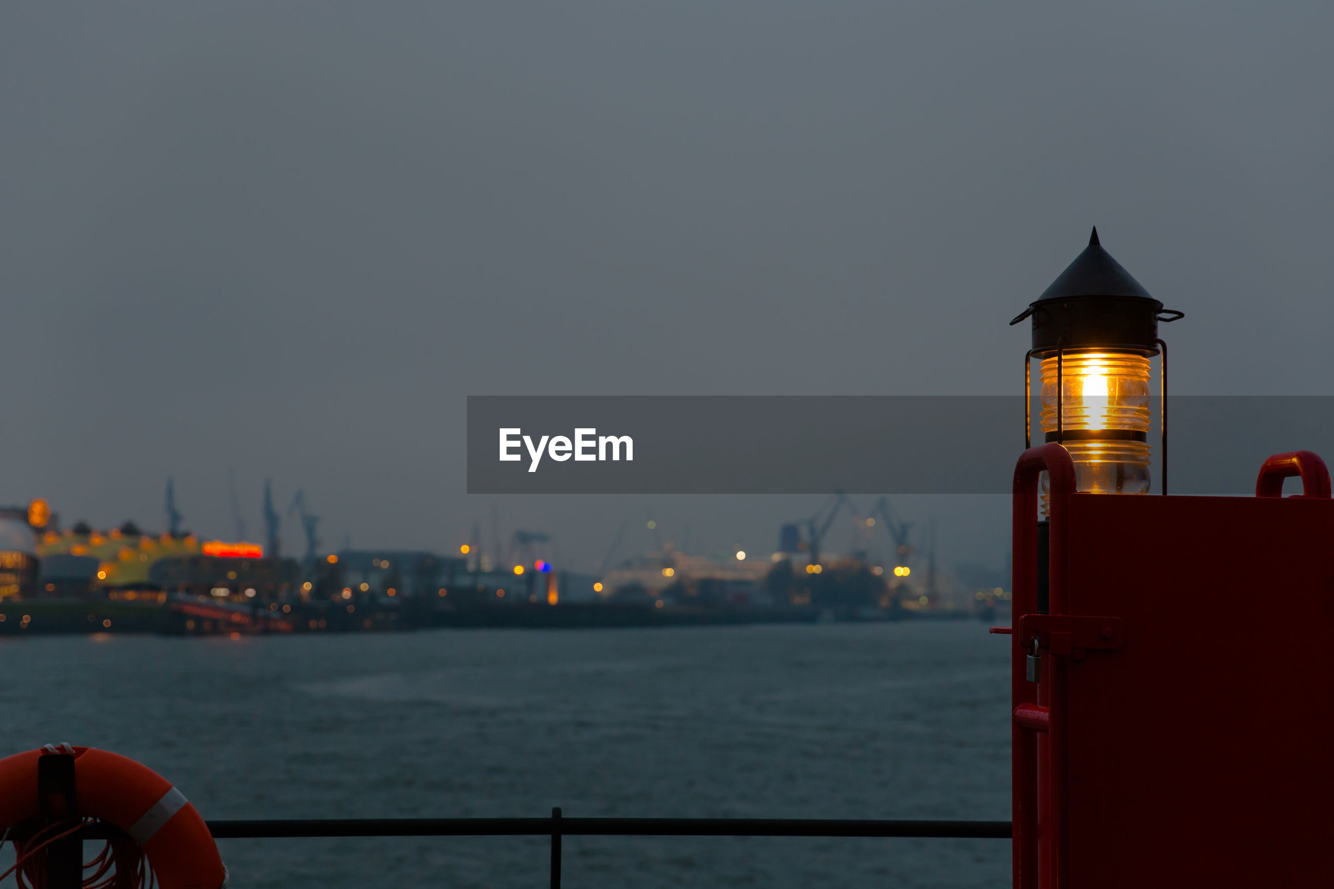 Illuminated lighthouse by elbe river against sky in city at dusk