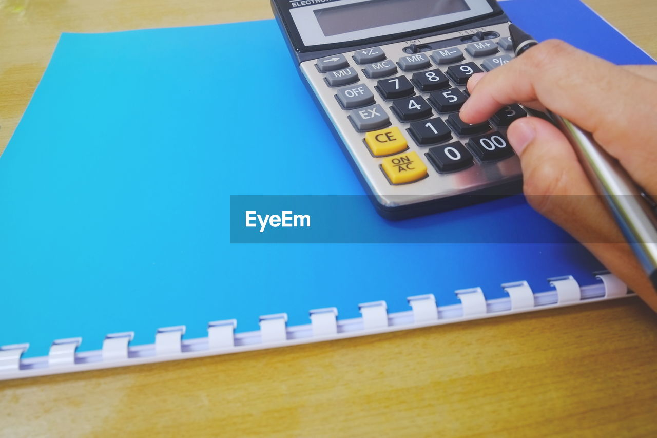Cropped hand of business person using calculator at desk in office