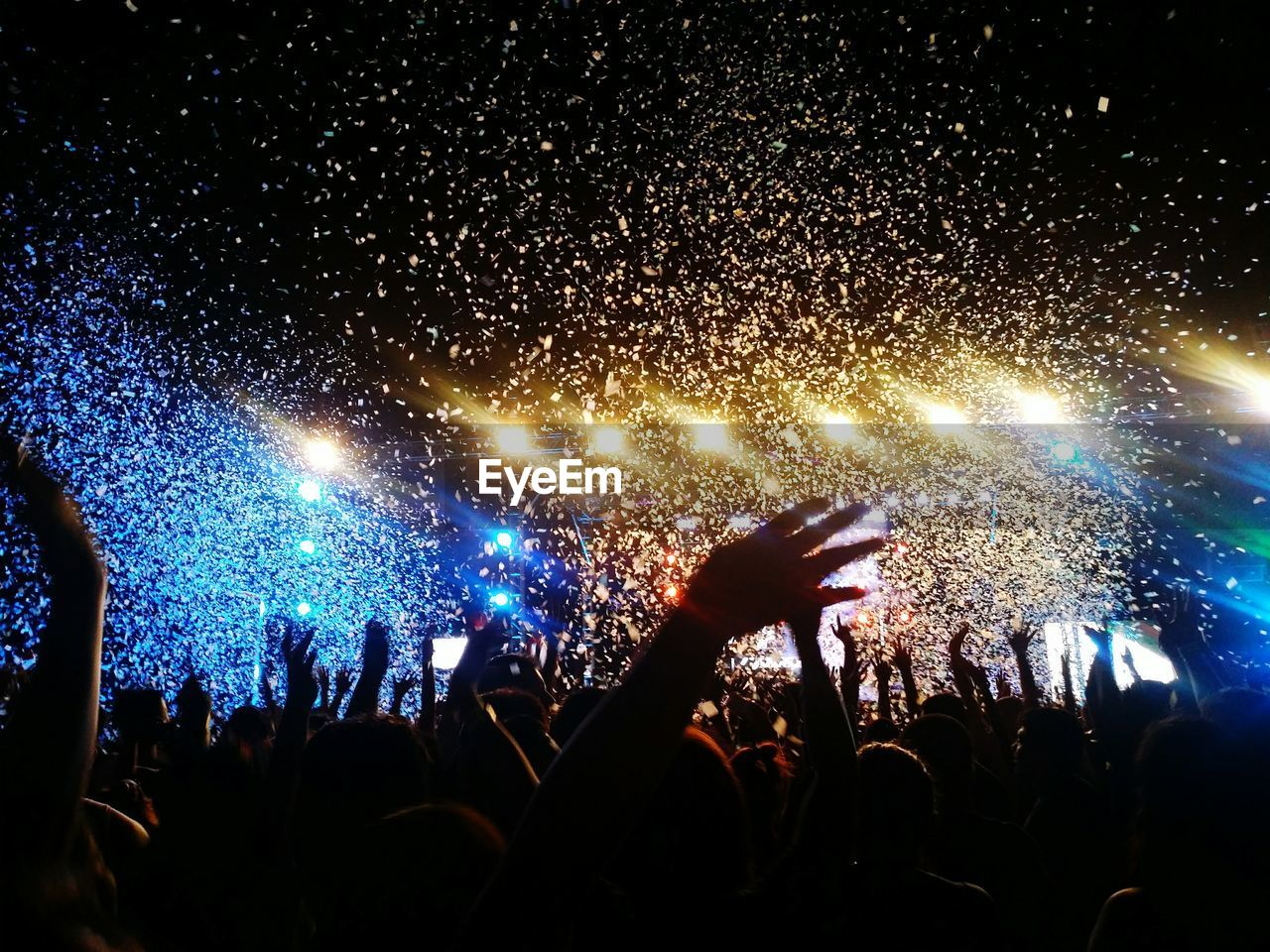 Crowd enjoying against illuminated stage with confetti during music concert