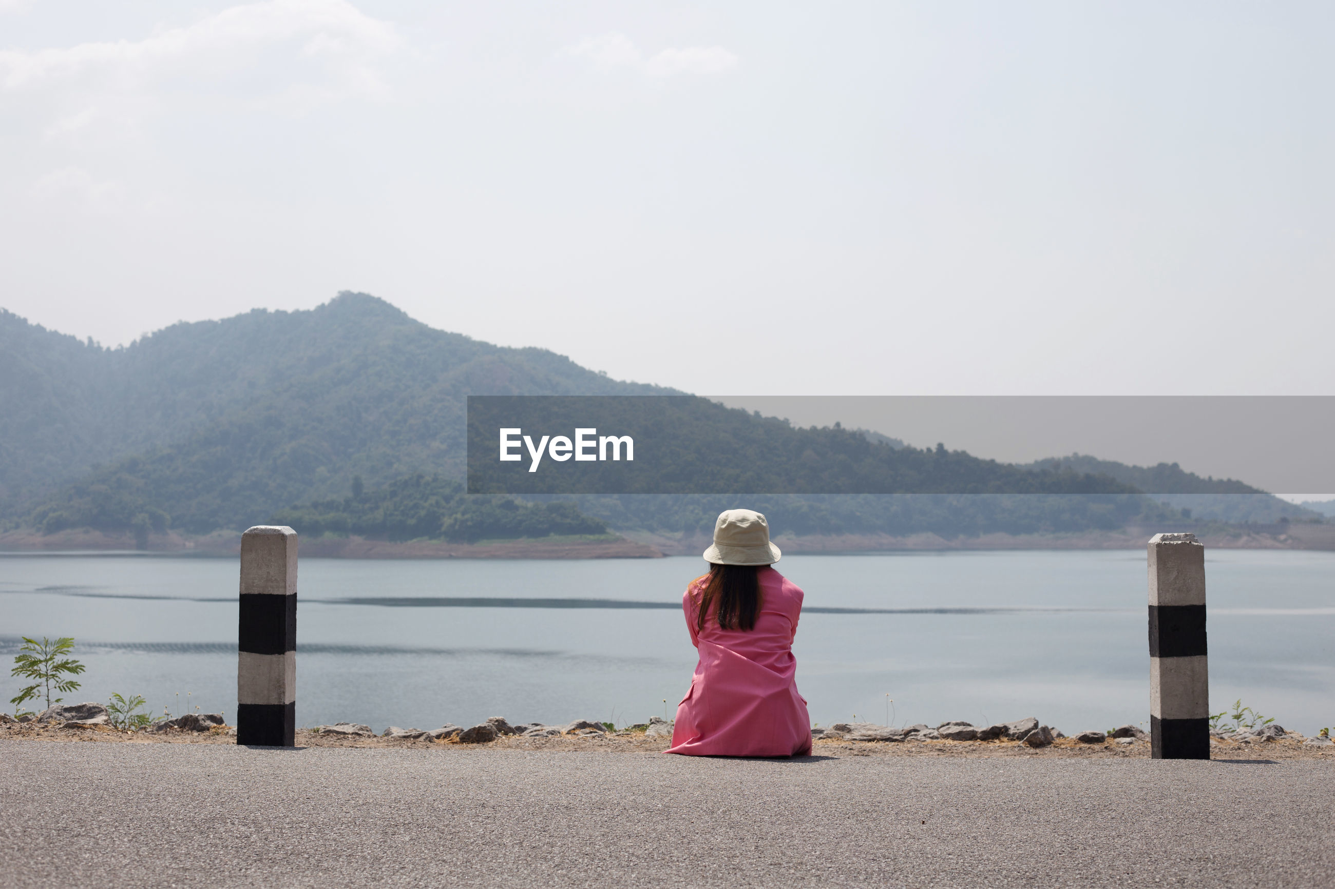 REAR VIEW OF WOMAN LOOKING AT SEA AGAINST MOUNTAIN RANGE