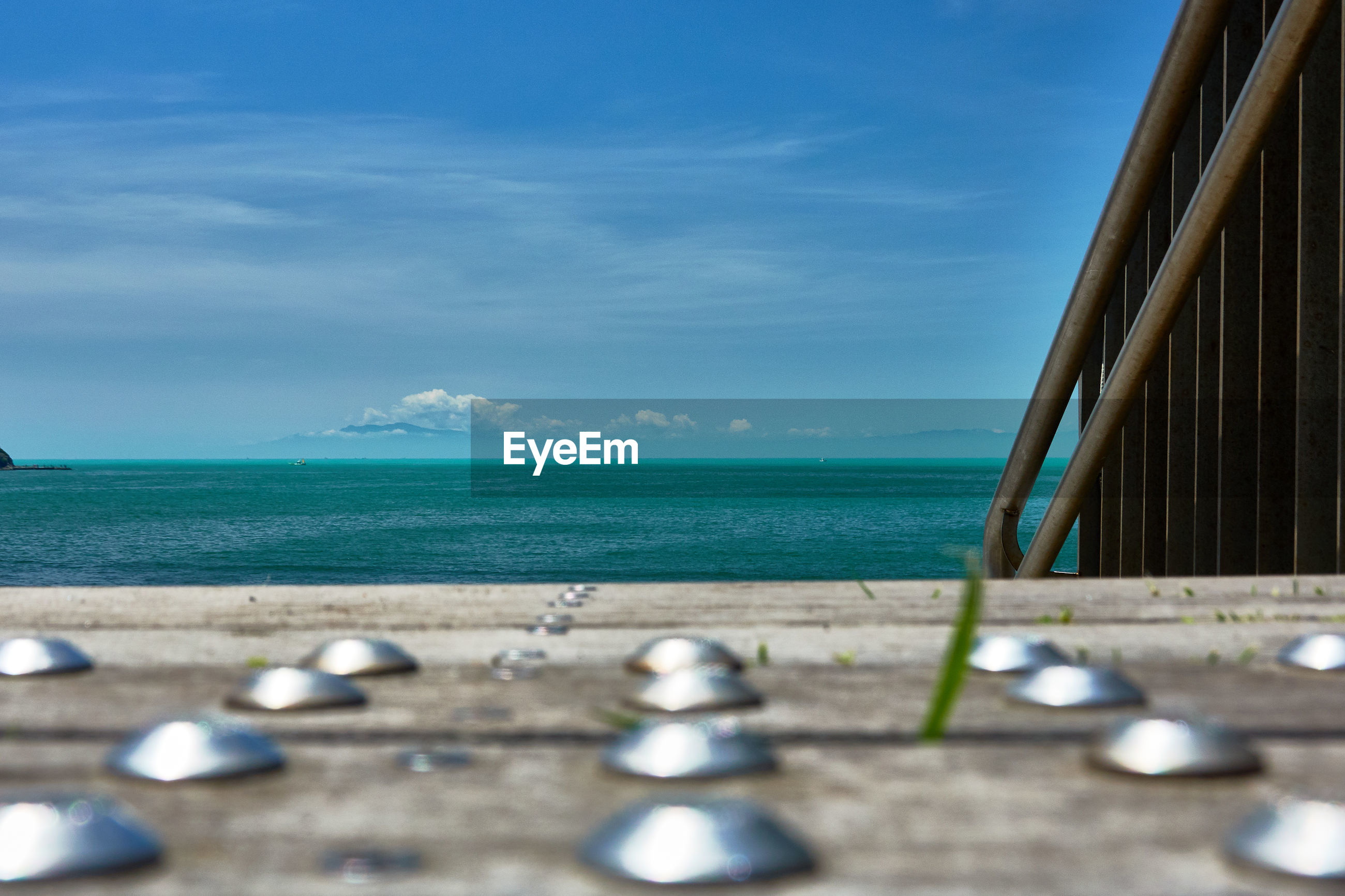 Scenic view of sea against sky with close up of  wooden deck