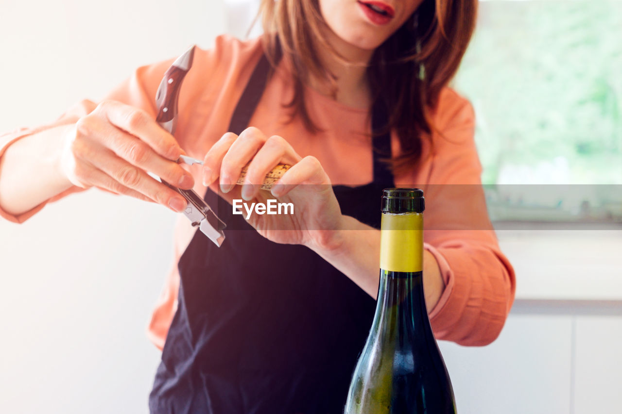 one person, holding, indoors, bottle, wine, alcohol, real people, wine bottle, lifestyles, front view, women, food and drink, focus on foreground, refreshment, adult, leisure activity, container, casual clothing, drink, midsection, glass, hairstyle, red wine, beautiful woman