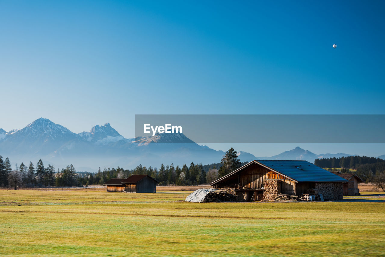 field, architecture, built structure, land, landscape, sky, plant, scenics - nature, mountain, building exterior, house, environment, grass, building, beauty in nature, no people, nature, farm, tranquil scene, tranquility, mountain range, outdoors