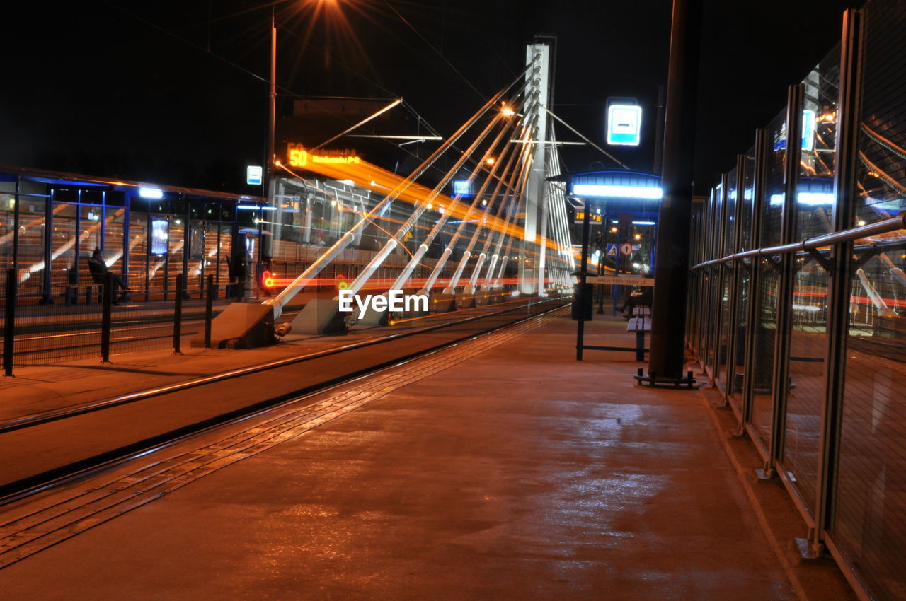 illuminated, night, transportation, architecture, motion, built structure, rail transportation, the way forward, no people, direction, lighting equipment, connection, city, long exposure, outdoors, public transportation, mode of transportation, blurred motion, railroad station, train