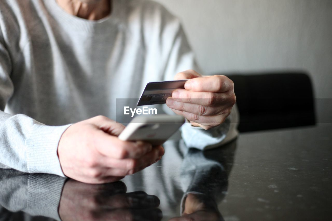 MIDSECTION OF MAN USING SMART PHONE IN LAPTOP