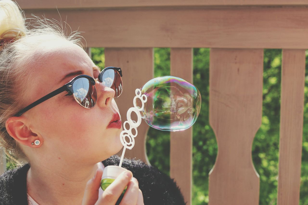 Close-up of teenage girl blowing bubble