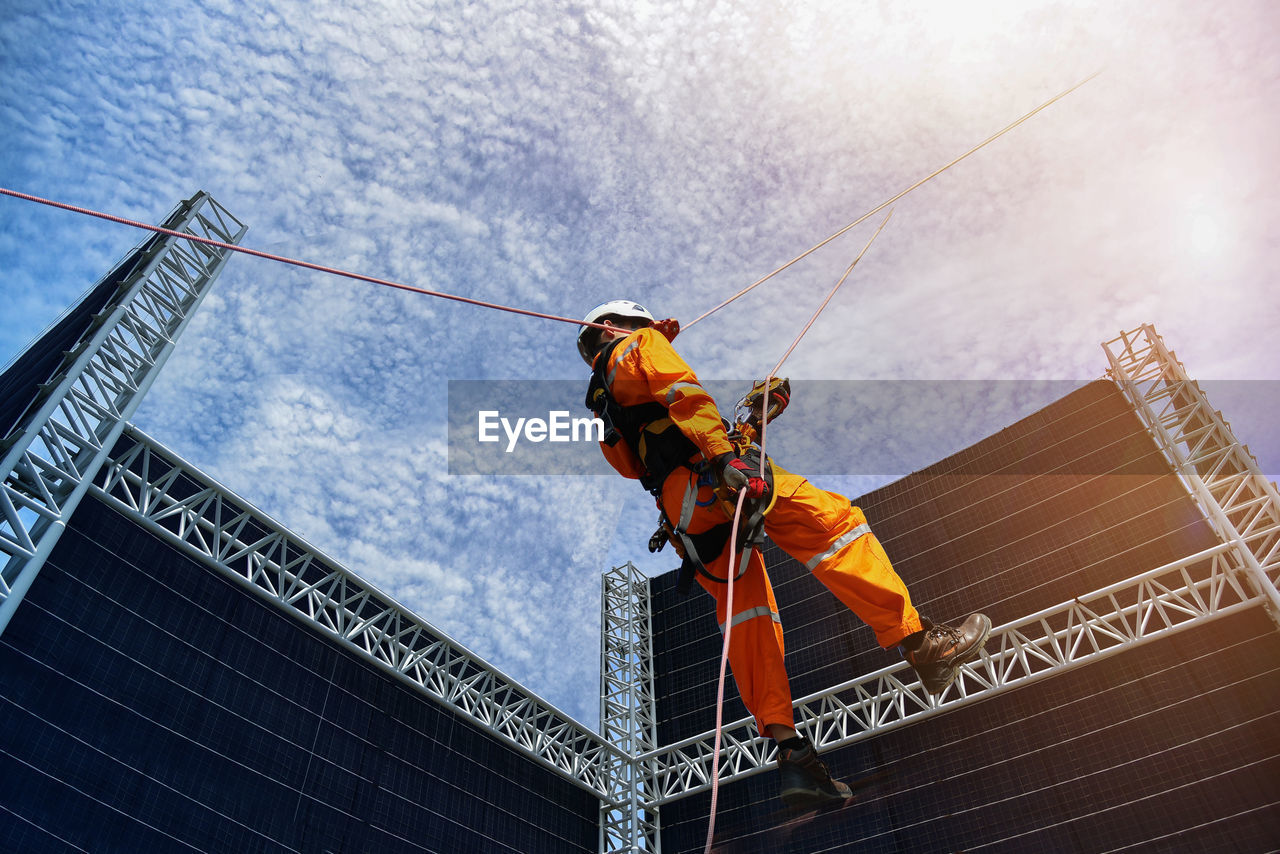 LOW ANGLE VIEW OF MAN WORKING ON CONSTRUCTION SITE