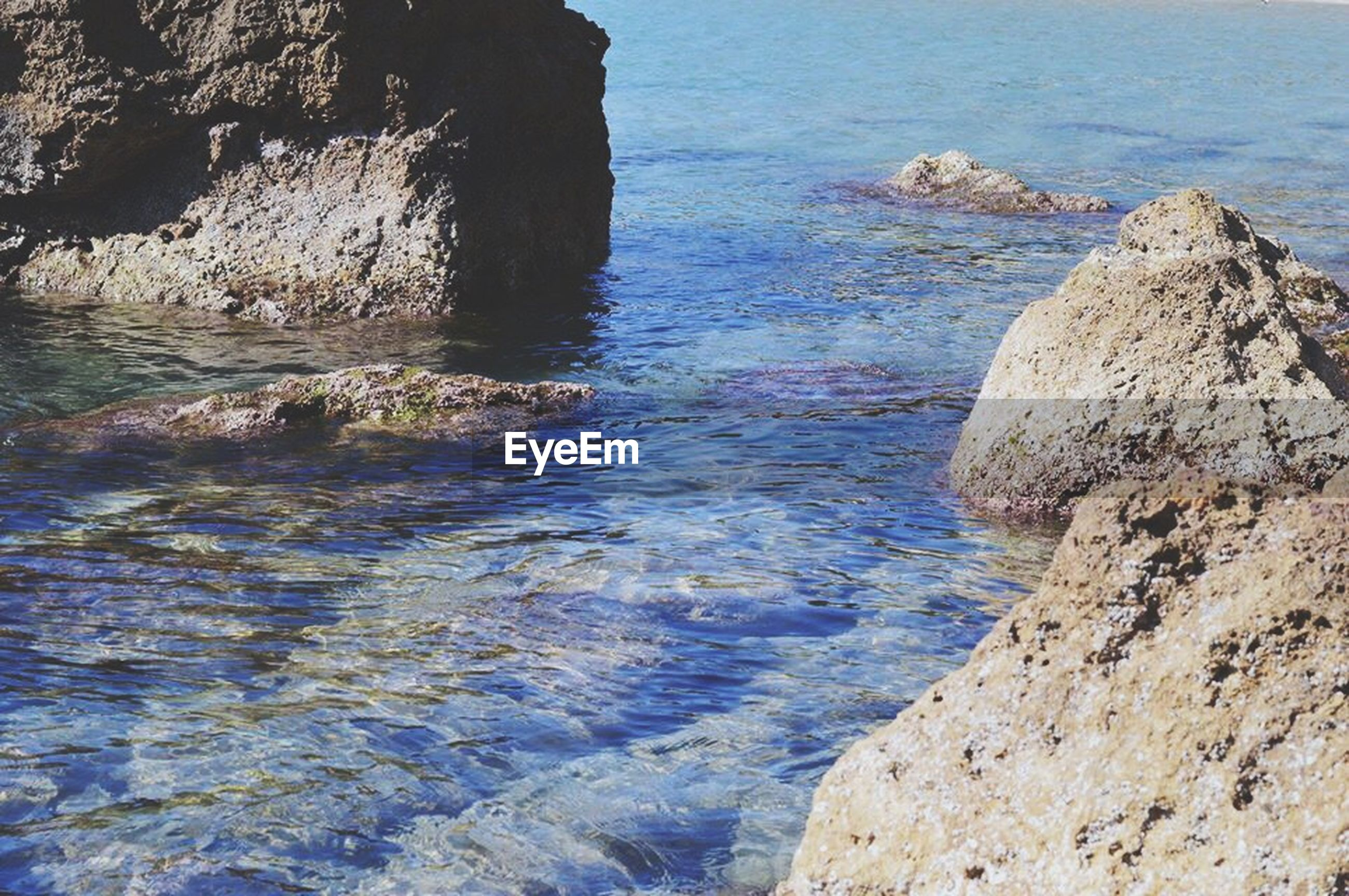 water, sea, rock - object, rock formation, beauty in nature, scenics, tranquility, tranquil scene, nature, rock, blue, cliff, high angle view, idyllic, day, horizon over water, sunlight, shore, rippled, outdoors
