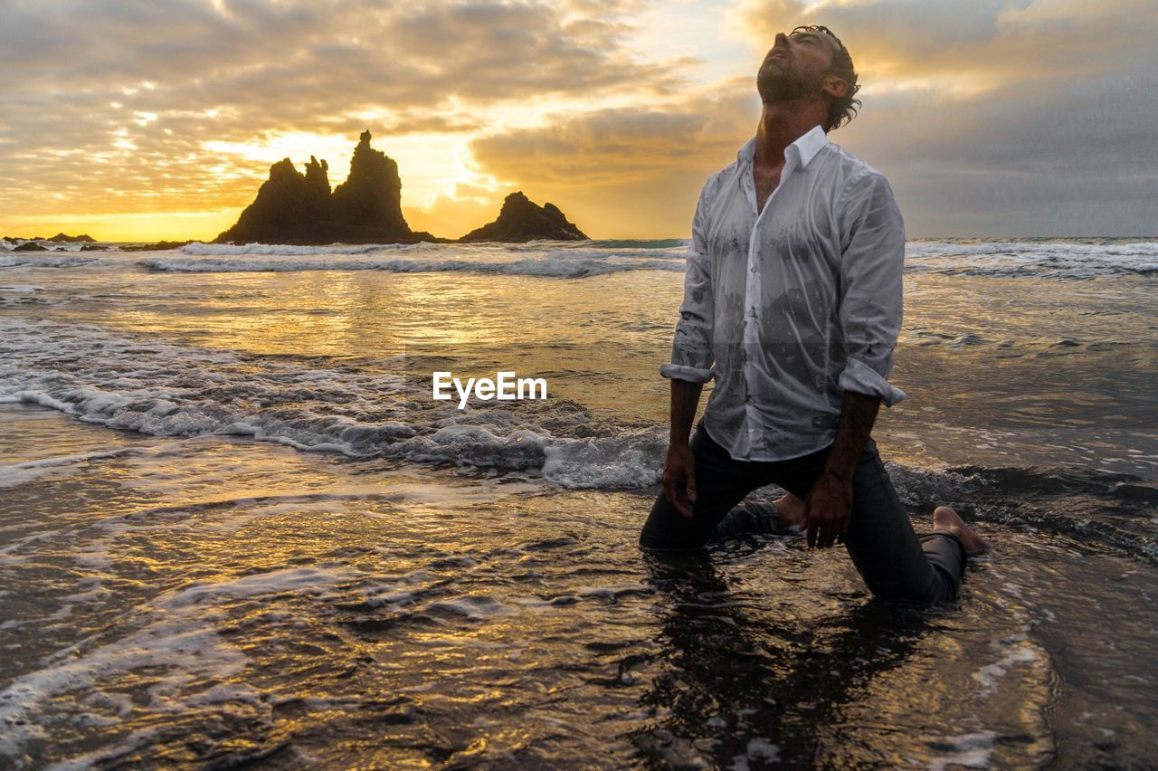 Scenic view of man in sea against cloudy sky at sunset