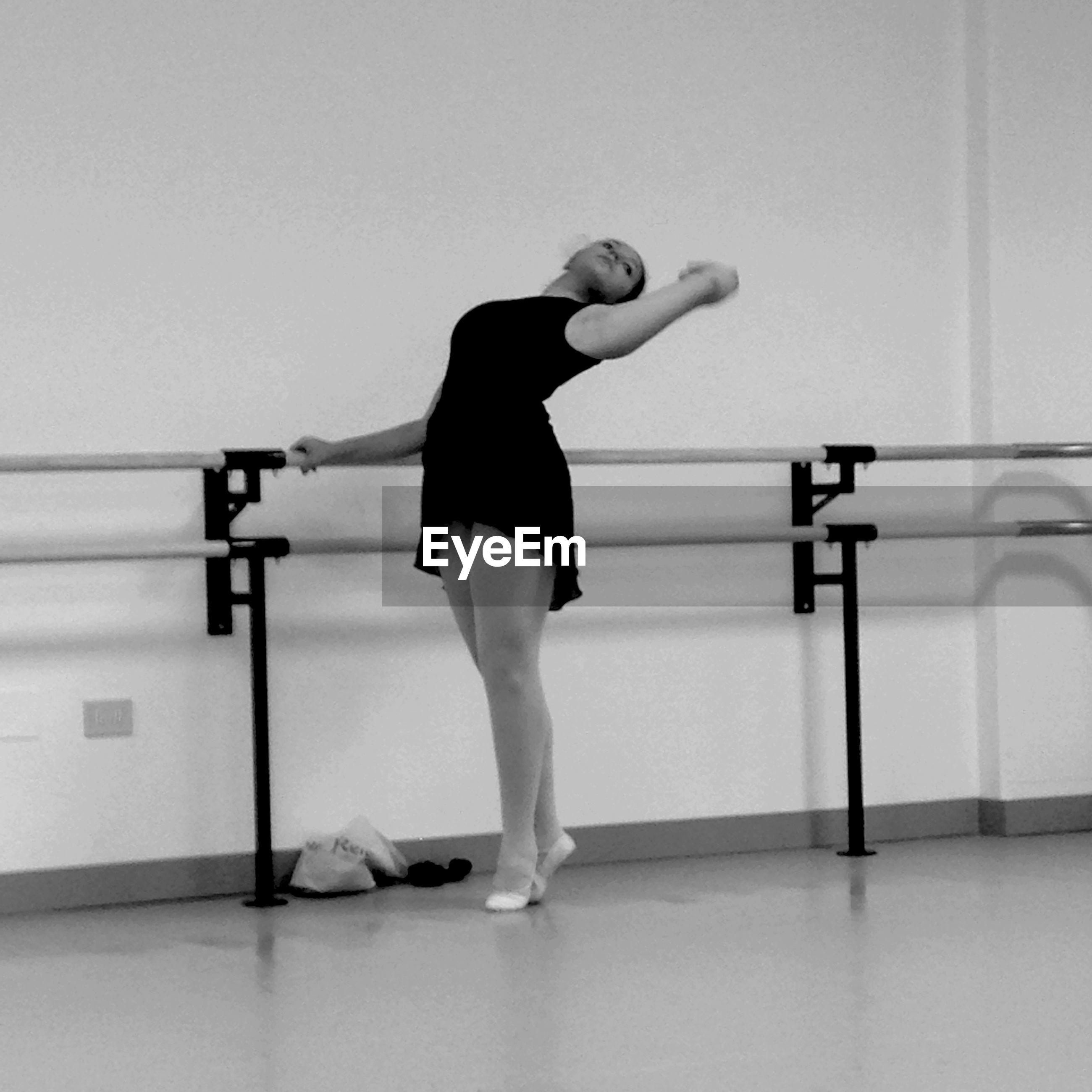 Full length of ballerina practicing at dance studio