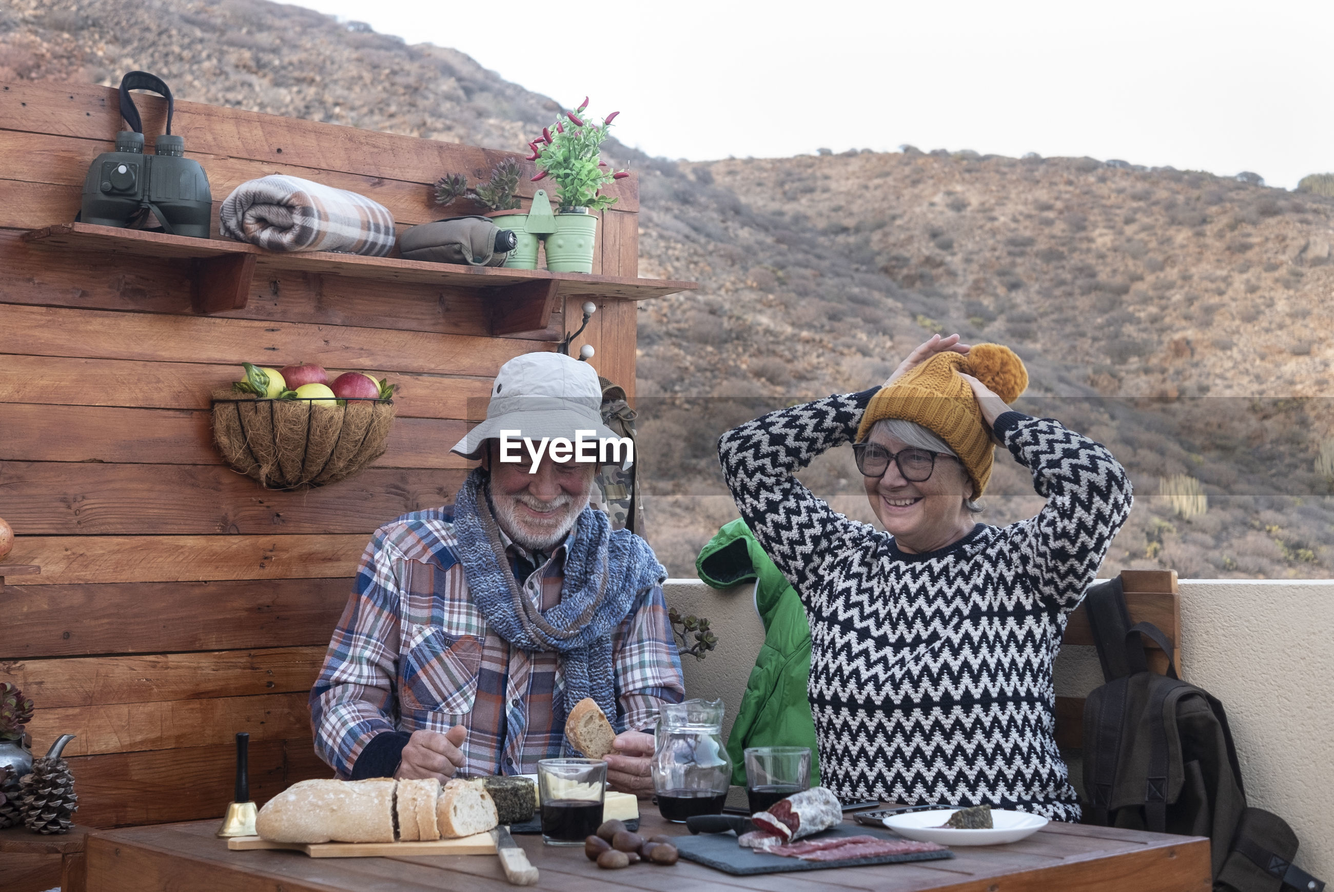Senior couple having food and drink while sitting on terrace