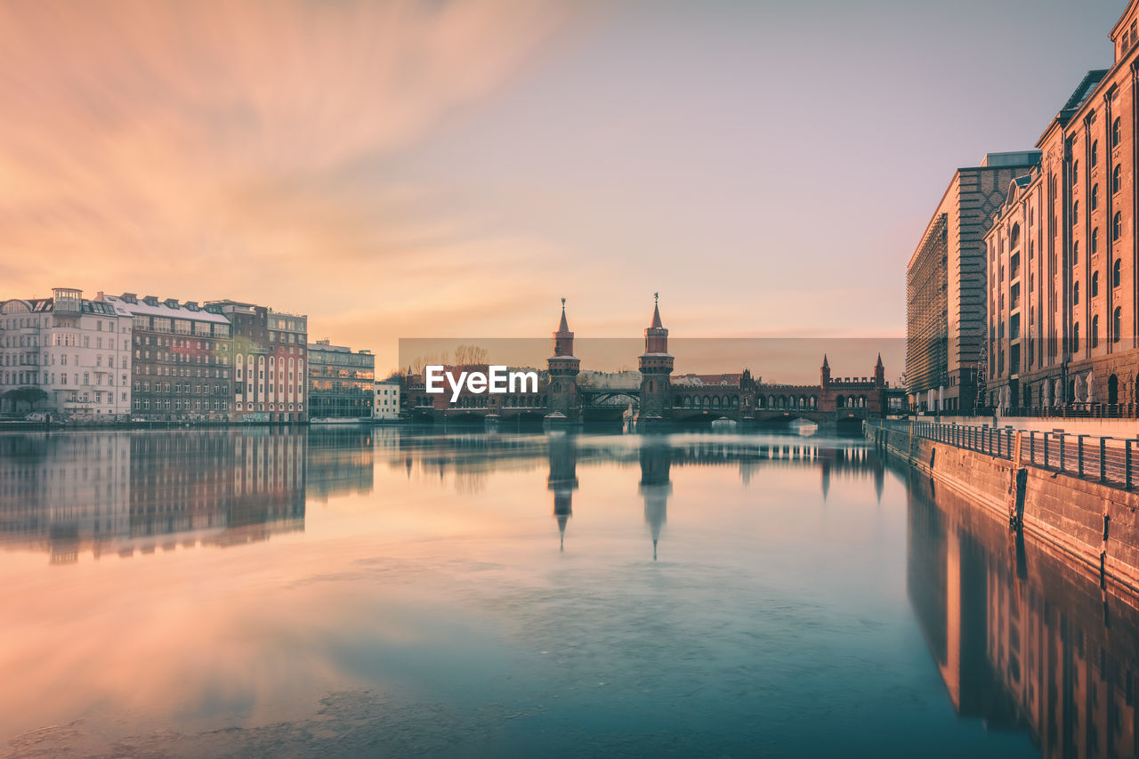 Oberbaum Bridge Over Spree River Amidst Buildings At Sunset