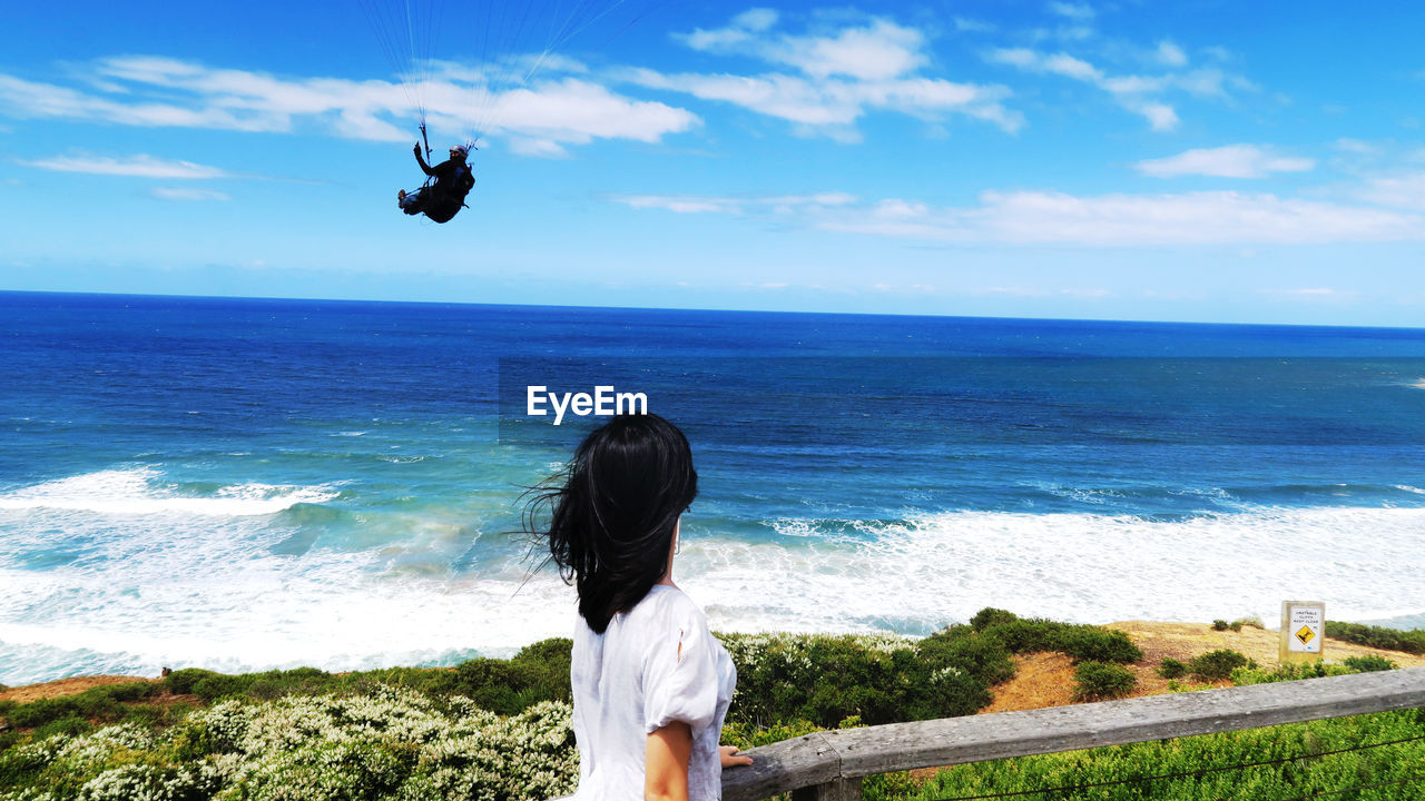 Side View Of Young Woman Looking At Man Paragliding At Beach Against Sky
